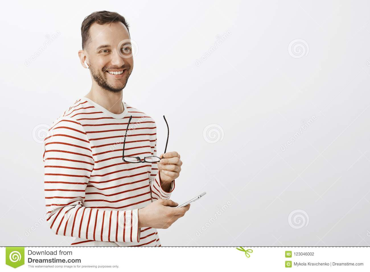 Positive successful male businessman, taking off glasses, looking aside and smiling friendly, picking music to listen in