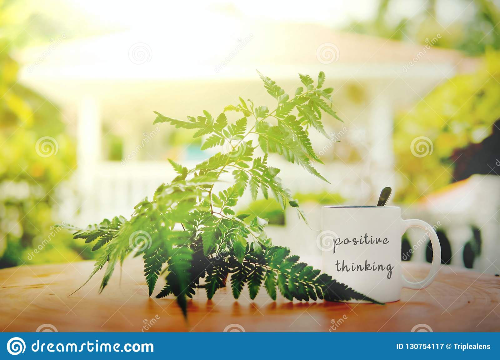 positive thinking words written at white mug on the wooden table against leaf and sun flare with blurry bokeh background