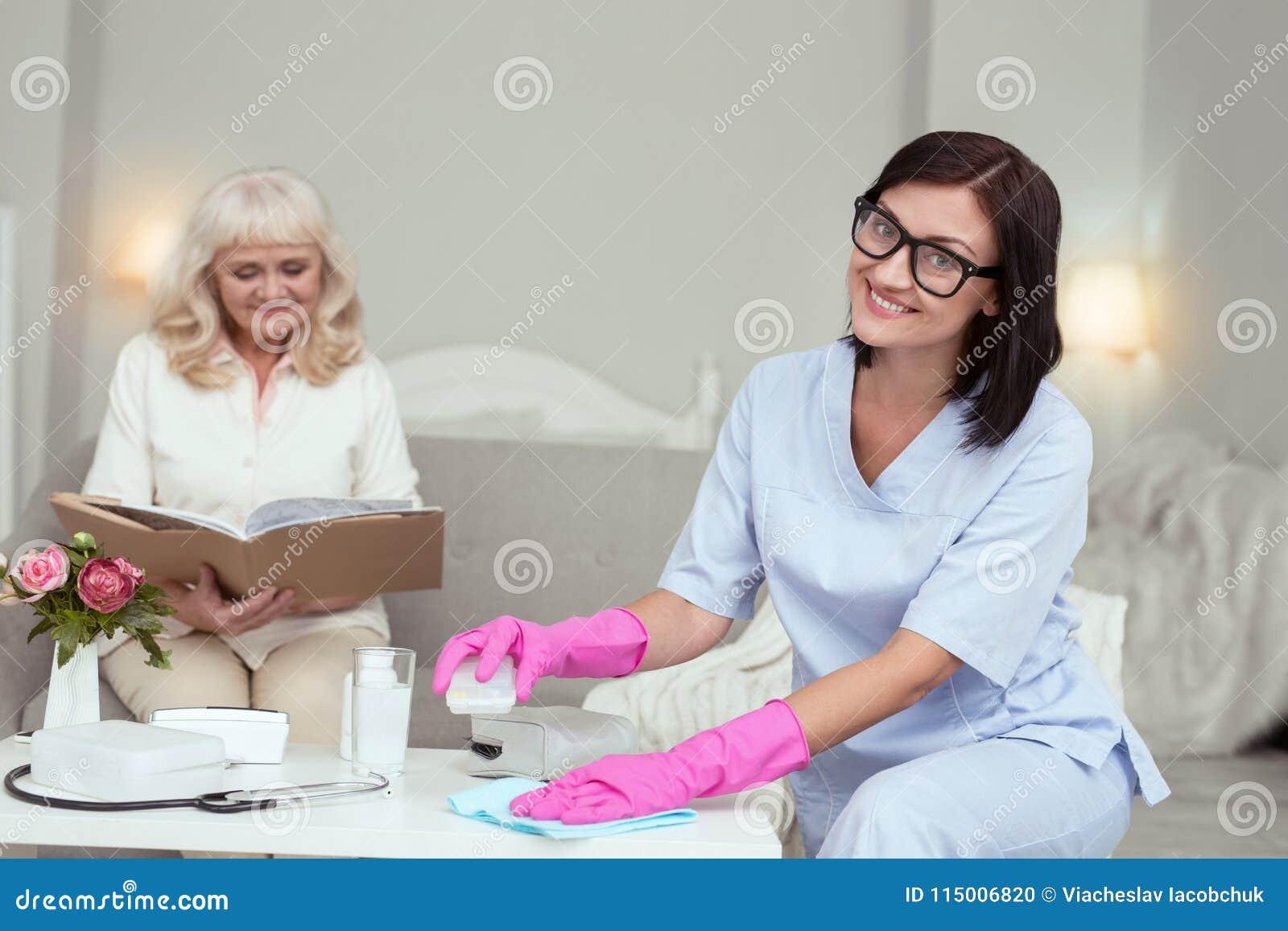 Positive weibliche Pflegekraft, die Staub entfernt