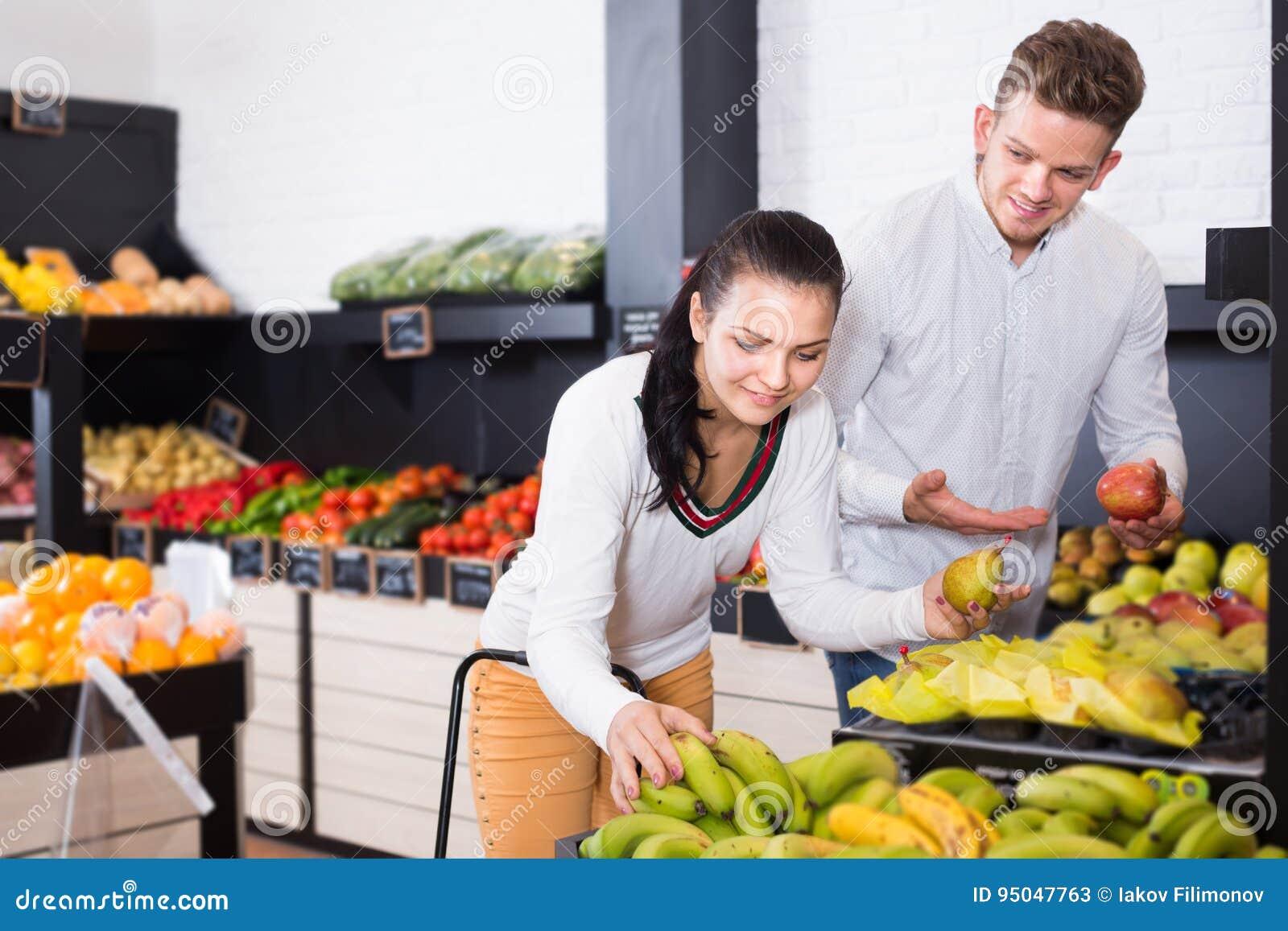 Positive woman and man choosing various fruits