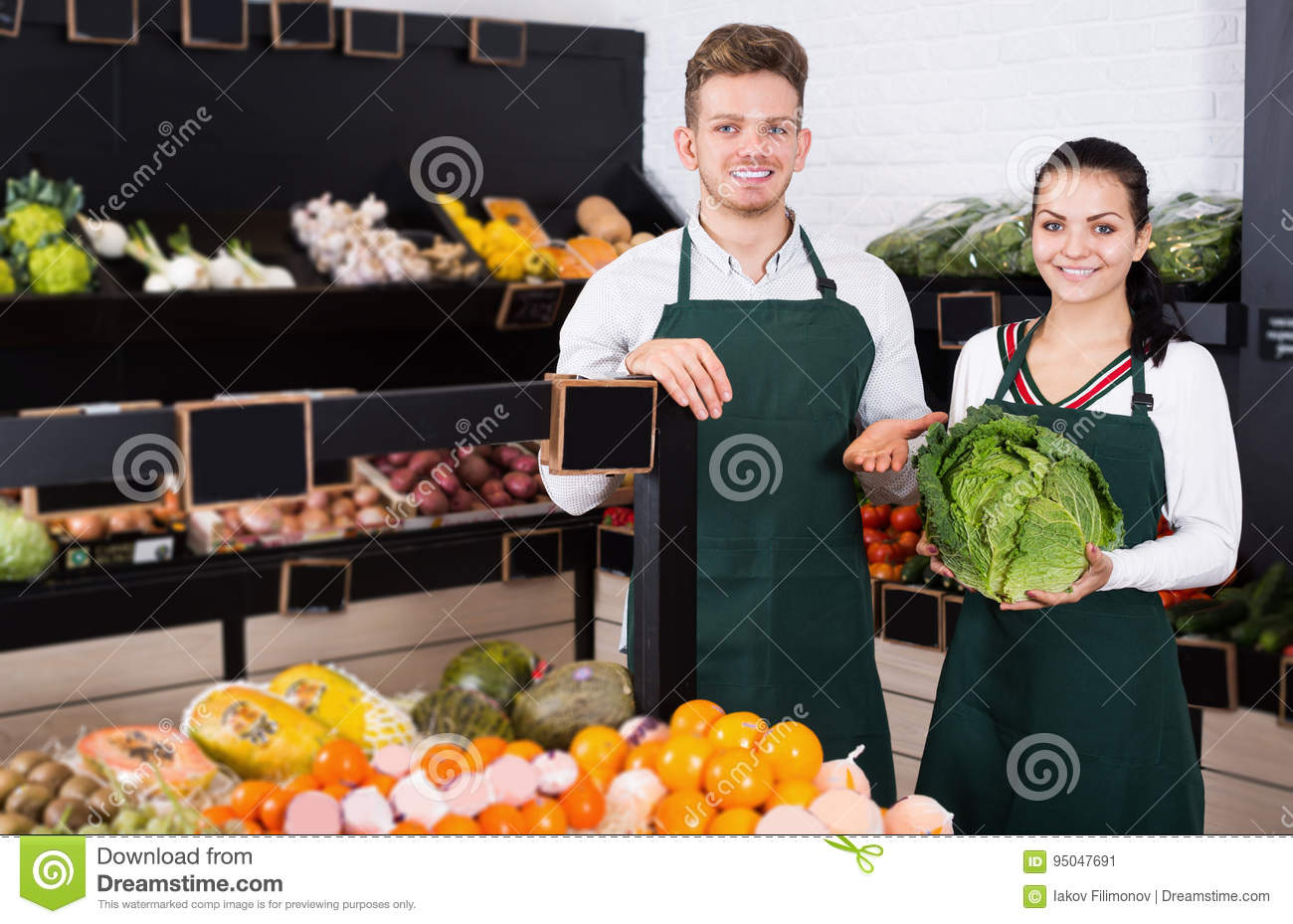 Positive young assistants displaying assortment