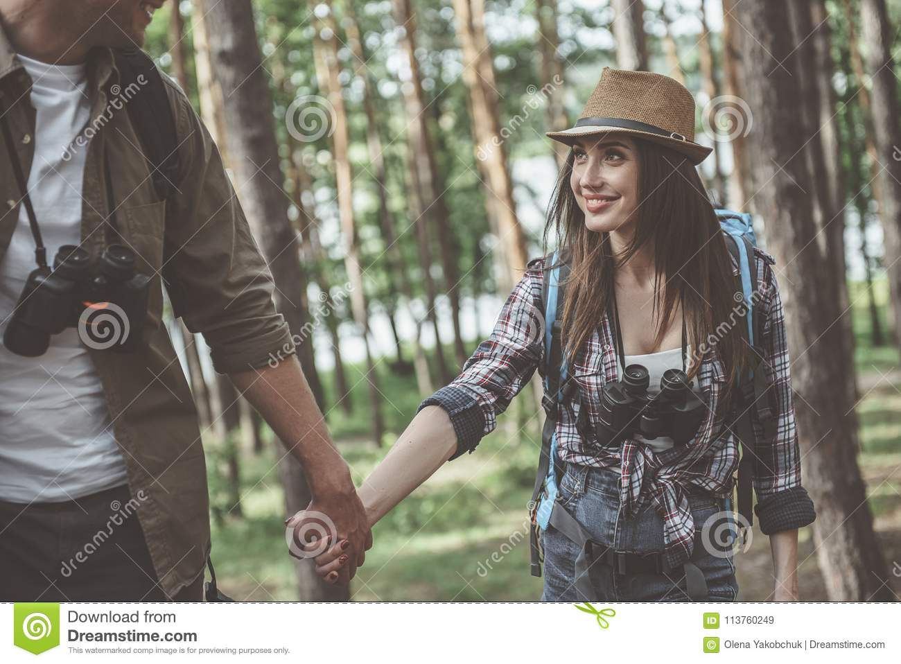 Positive young couple in love is walking in forest