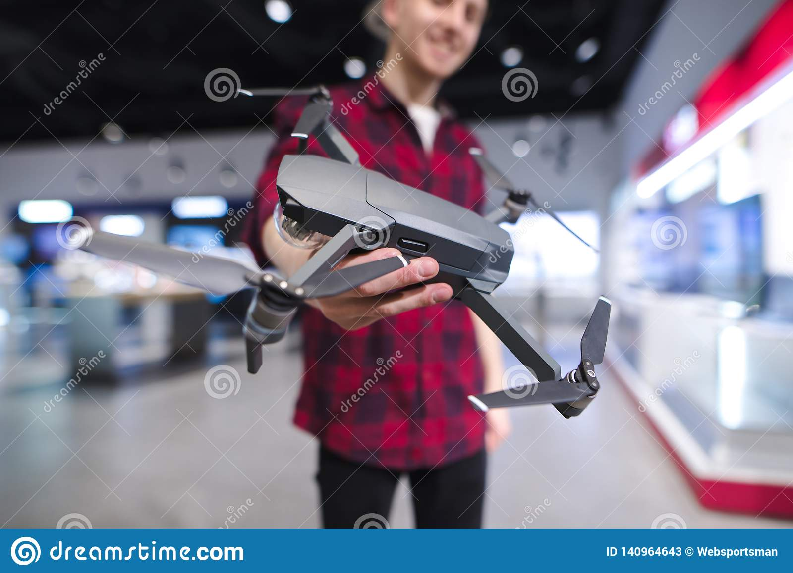 positive young man with a quadcopter in his hands is in the drones store. Buy a dron at an electronics store