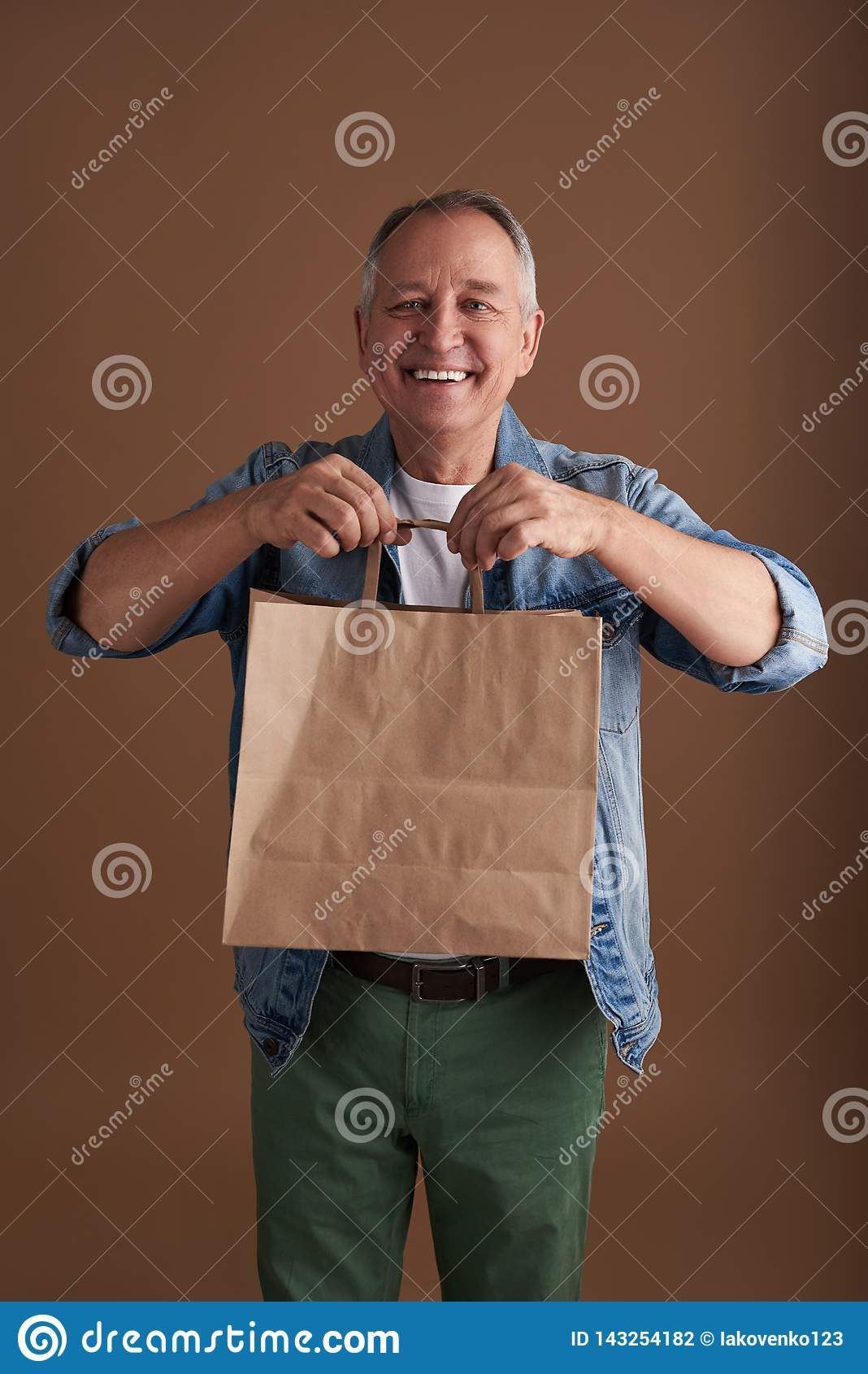 Positivt mananseende med papperspåsen och rymma dess handtag