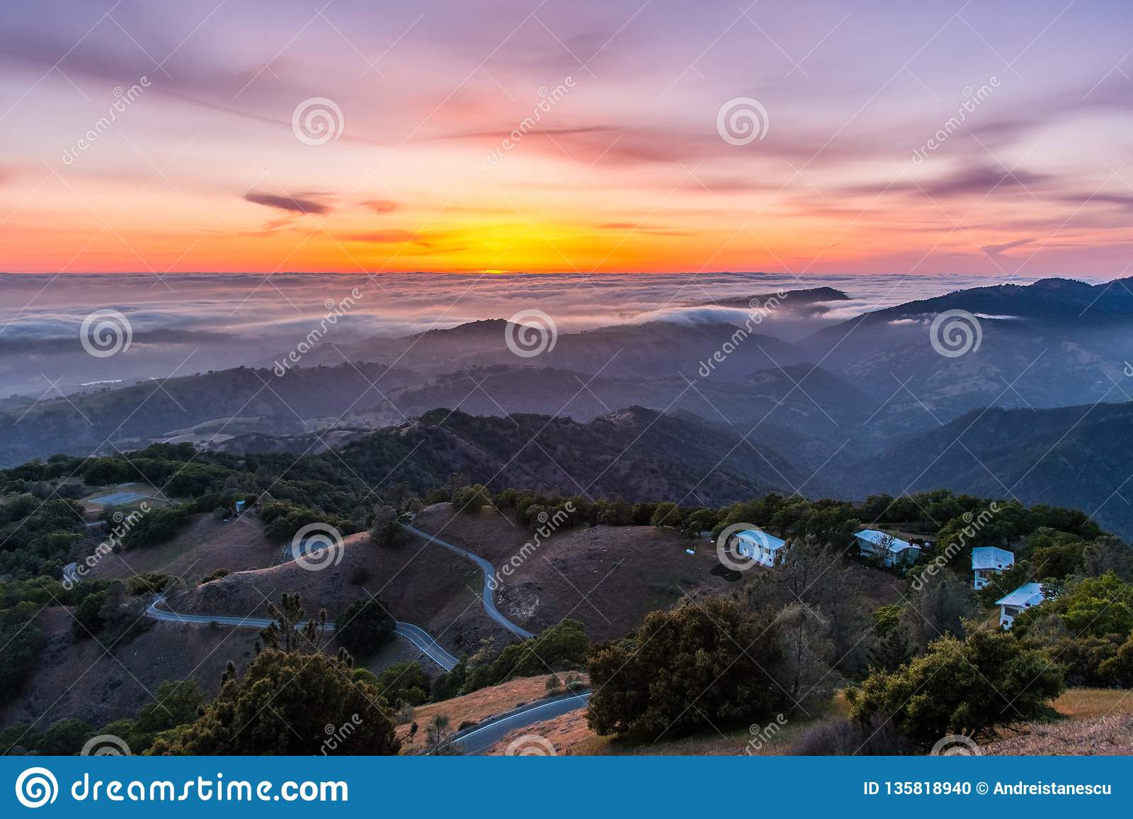 Posluminiscencia de la puesta del sol sobre un mar de nubes; carretera con curvas que desciende a través de Rolling Hills en el p