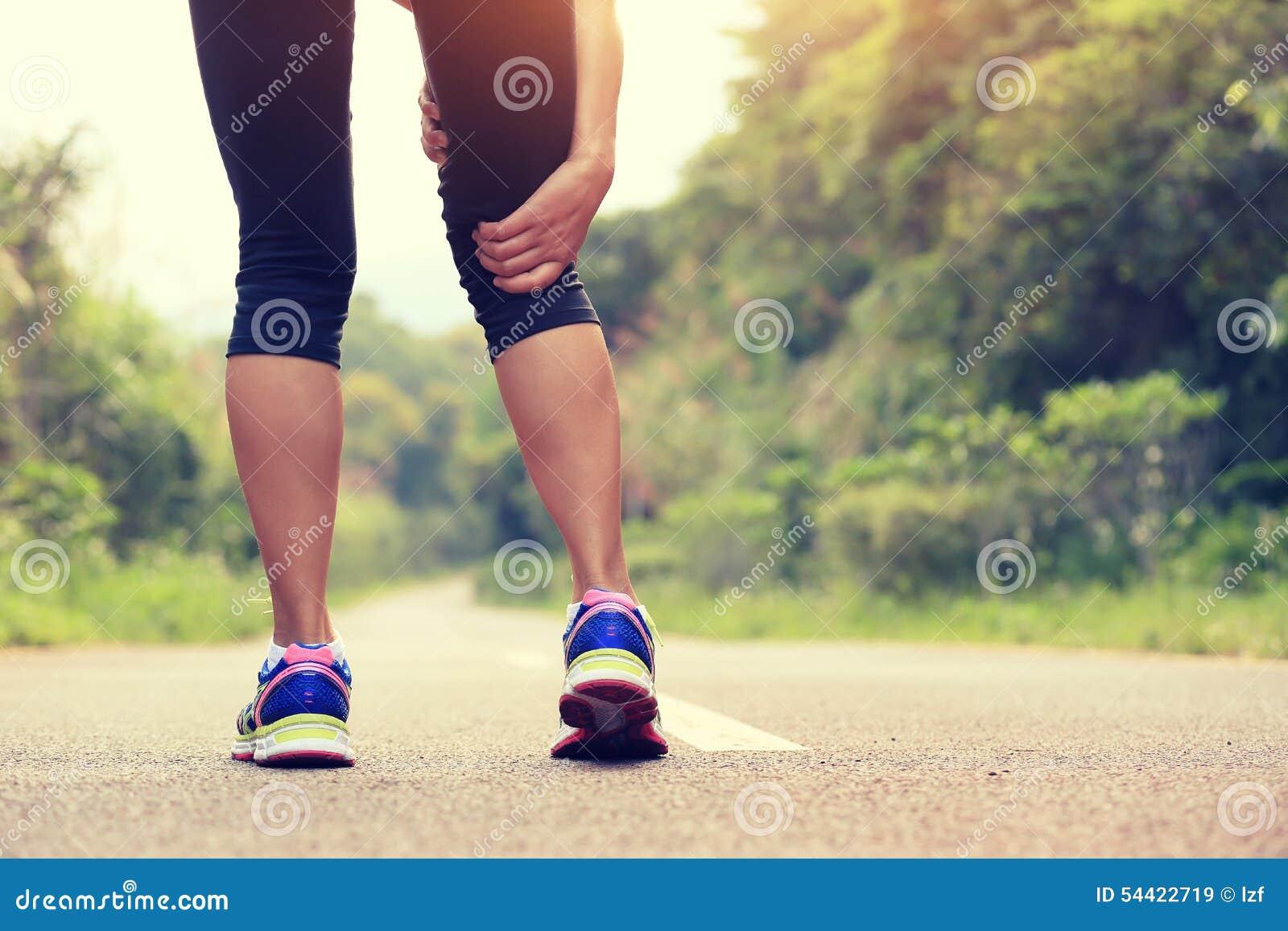 A posse do basculador da mulher da aptidão seus esportes feriu o pé na fuga da floresta