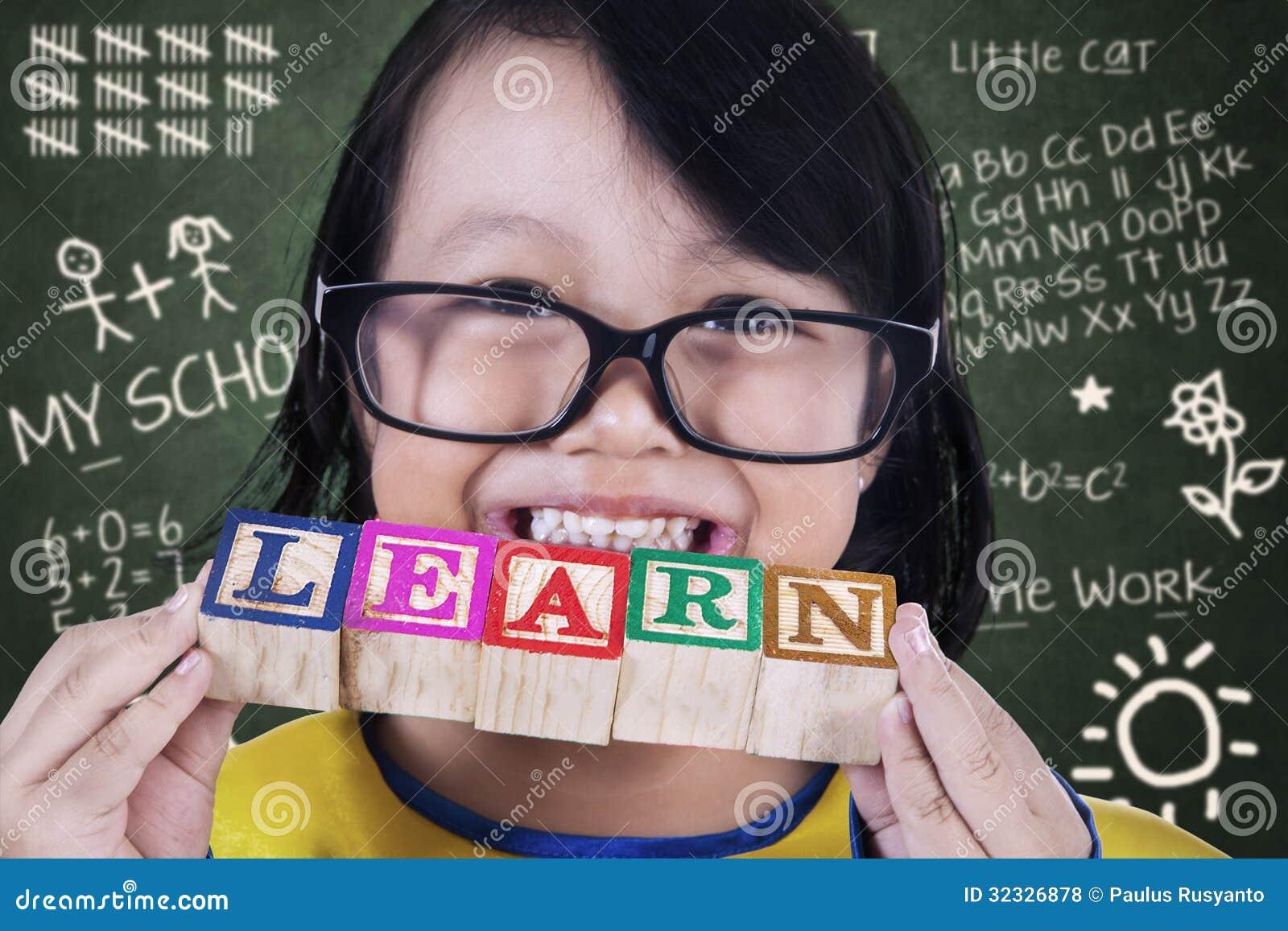 A posse do graduado da menina do close-up aprende o brinquedo de madeira na classe