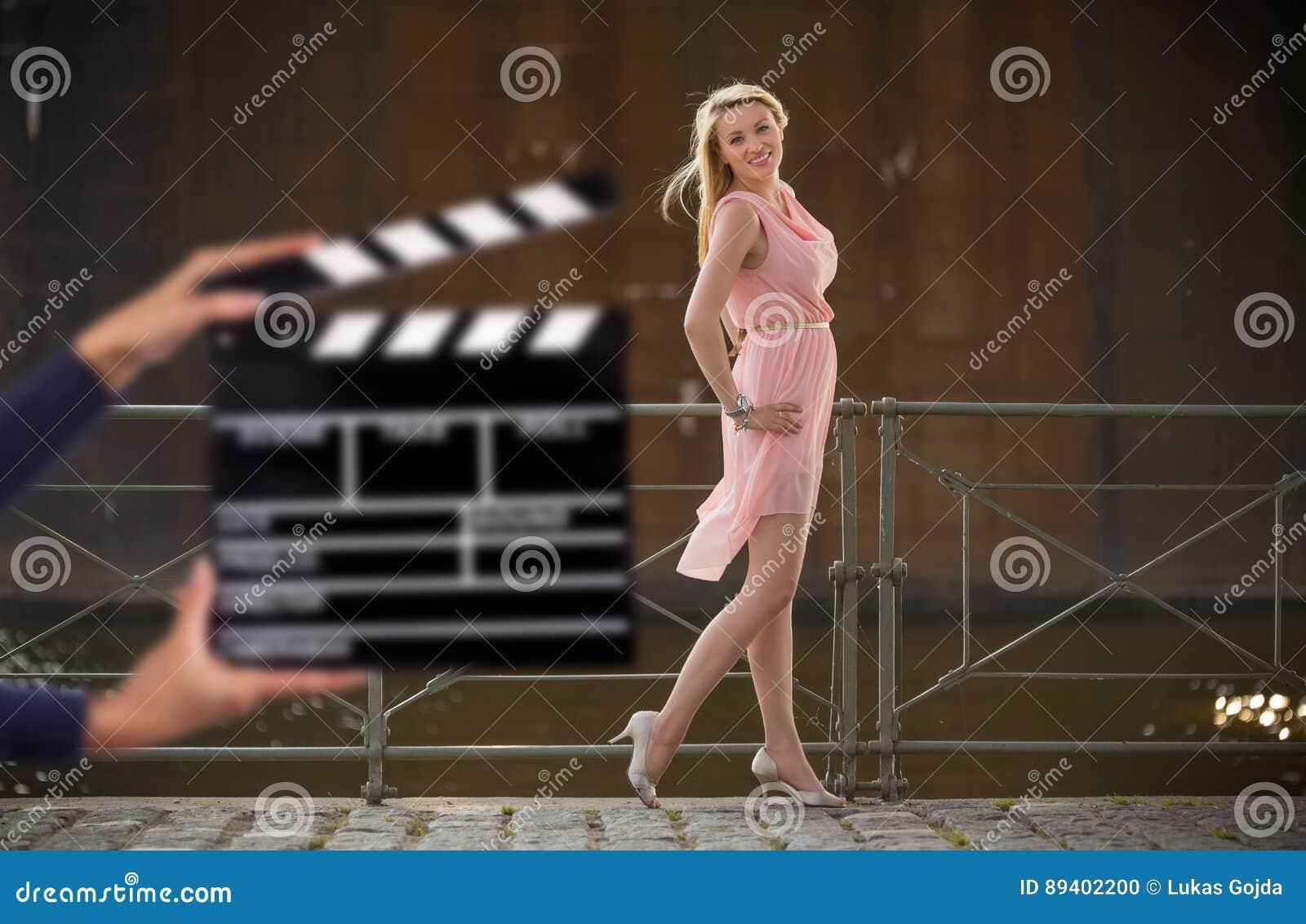 Posse do sinal de Clapperboard pelas mãos fêmeas