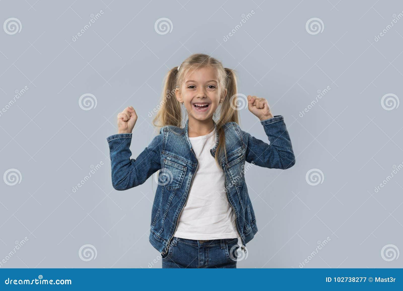 A posse entusiasmado da menina bonita entrega acima do revestimento de sorriso feliz das calças de brim do desgaste isolado