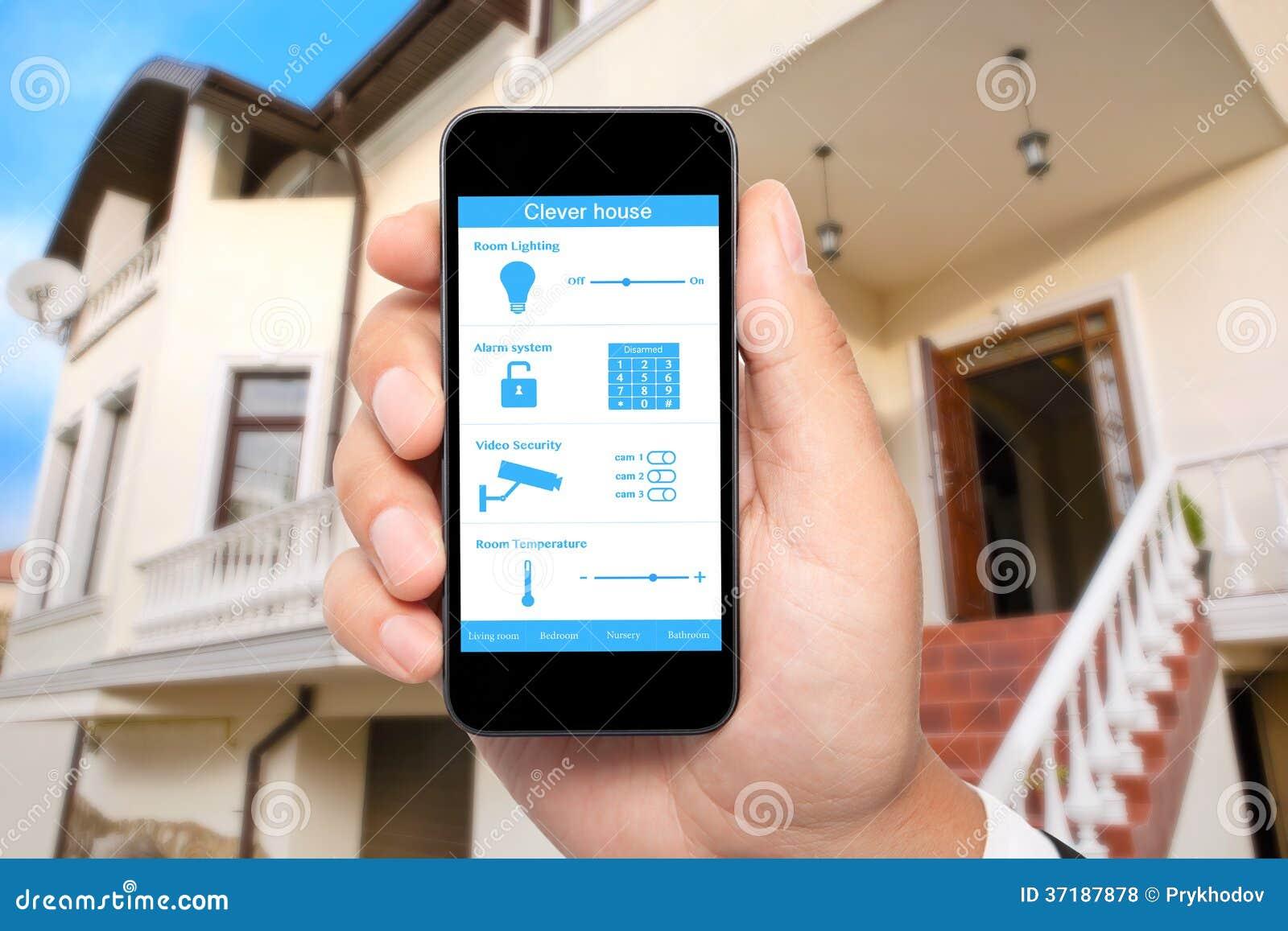 Posse masculina da mão um telefone com a casa inteligente do sistema no backgroun
