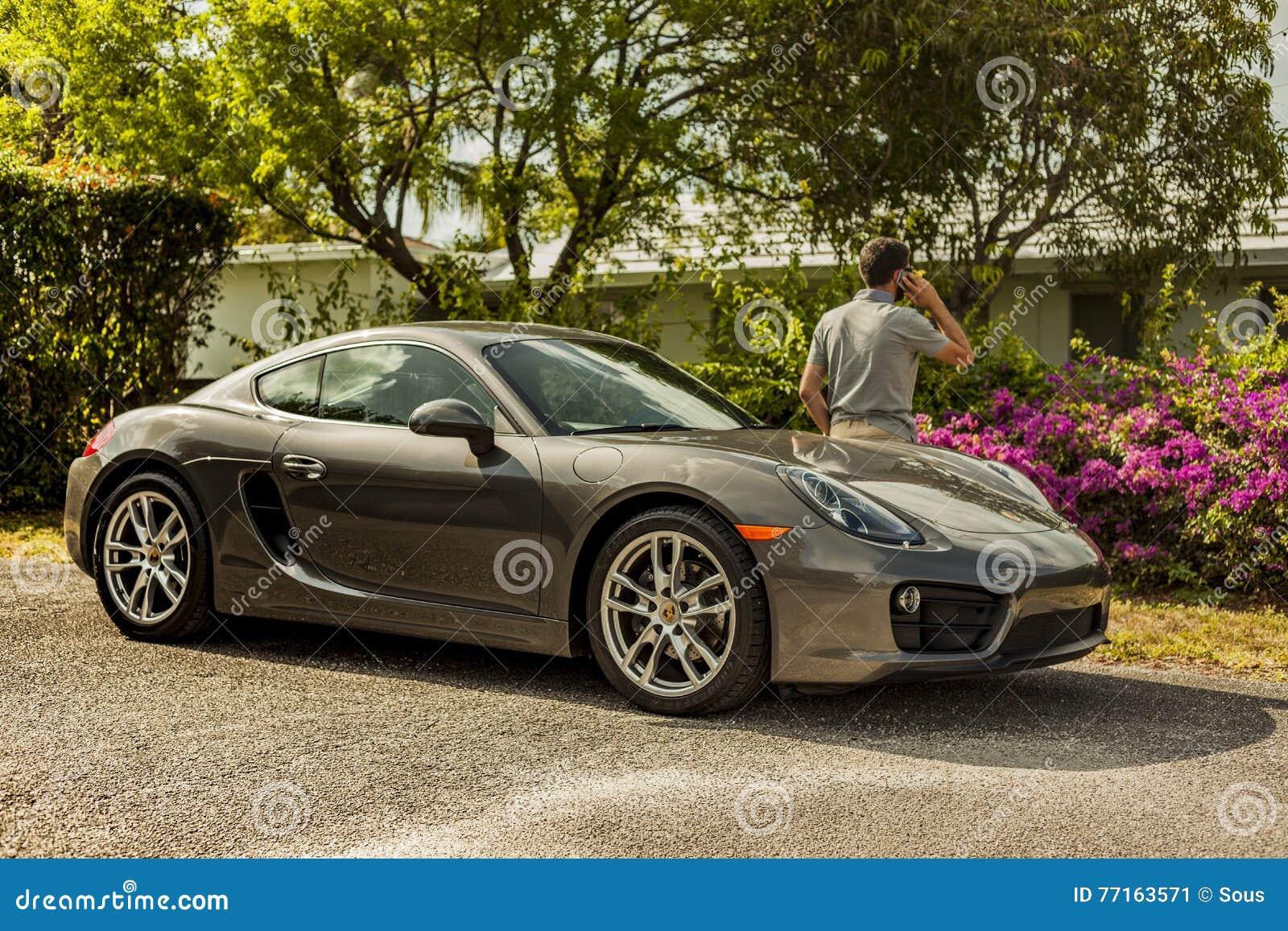 Possibilité éloignée d un jeune homme au téléphone, maigre sur Porsche Cayman
