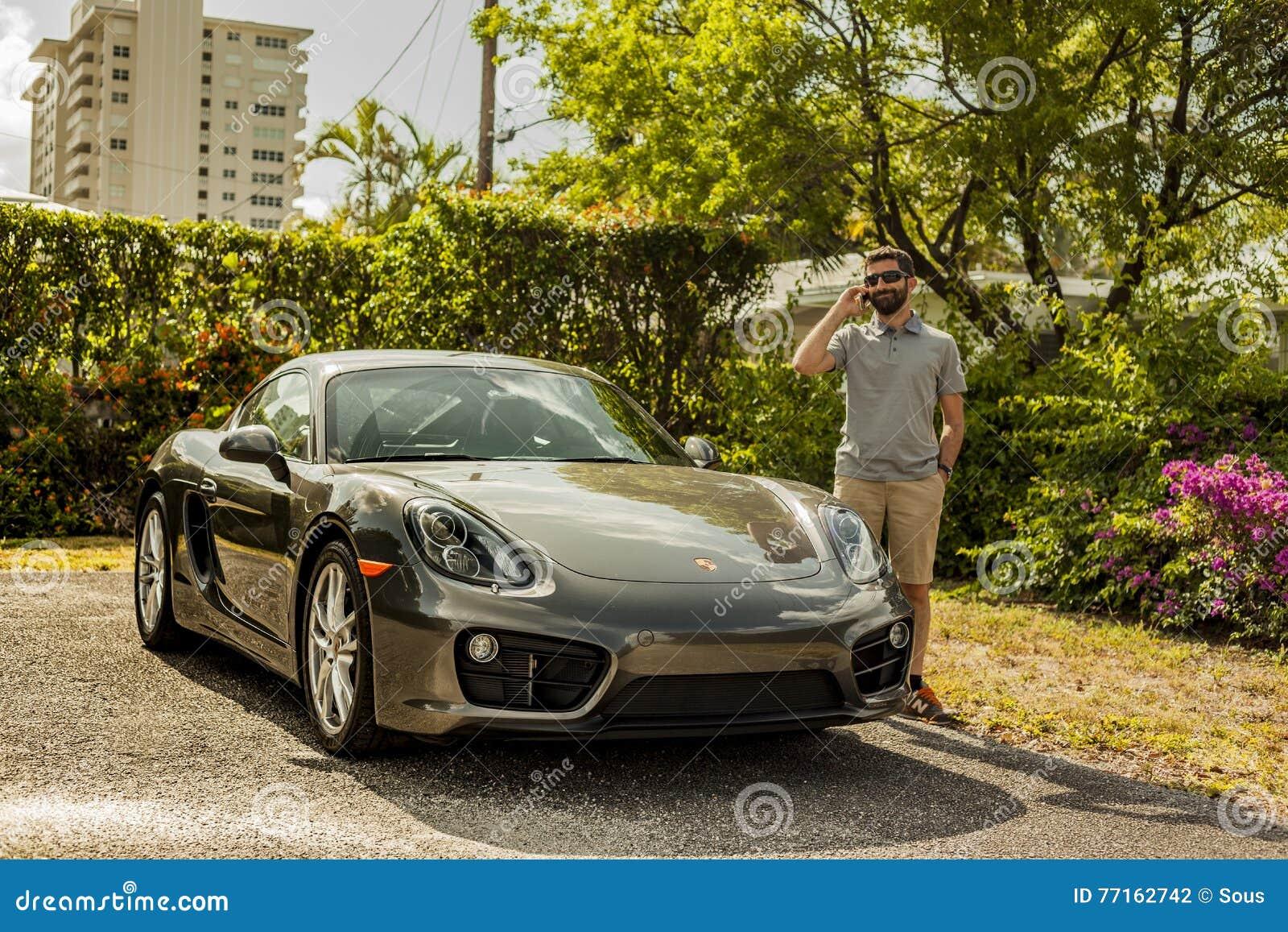 Possibilité éloignée d un jeune homme au téléphone, se tenant prêt un banc de sable de Porsche