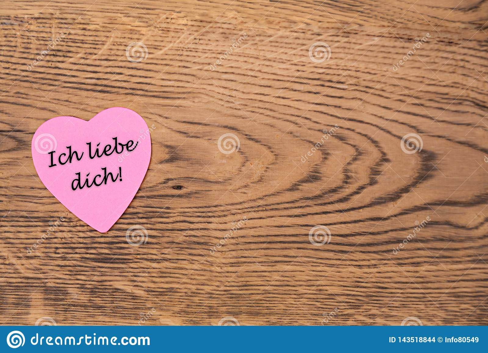 Post-it rosado del corazón con el texto 'dich del liebe de Ich 'en un fondo de madera Traducci?n: ?Te amo ?