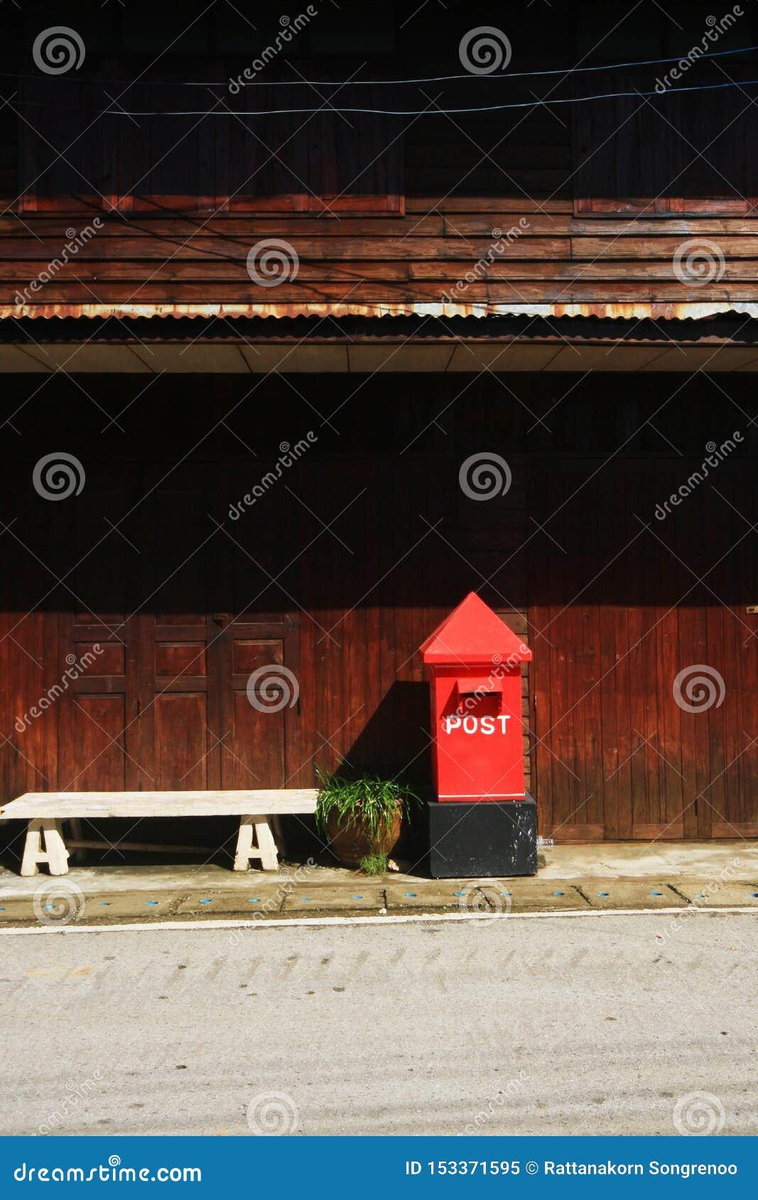 Postbox rosso sul sentiero per pedoni alla campagna in Tailandia