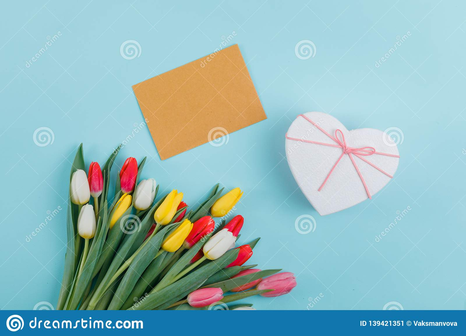 Spring tulips frame on background, top view. Postcard for Women`s Day.