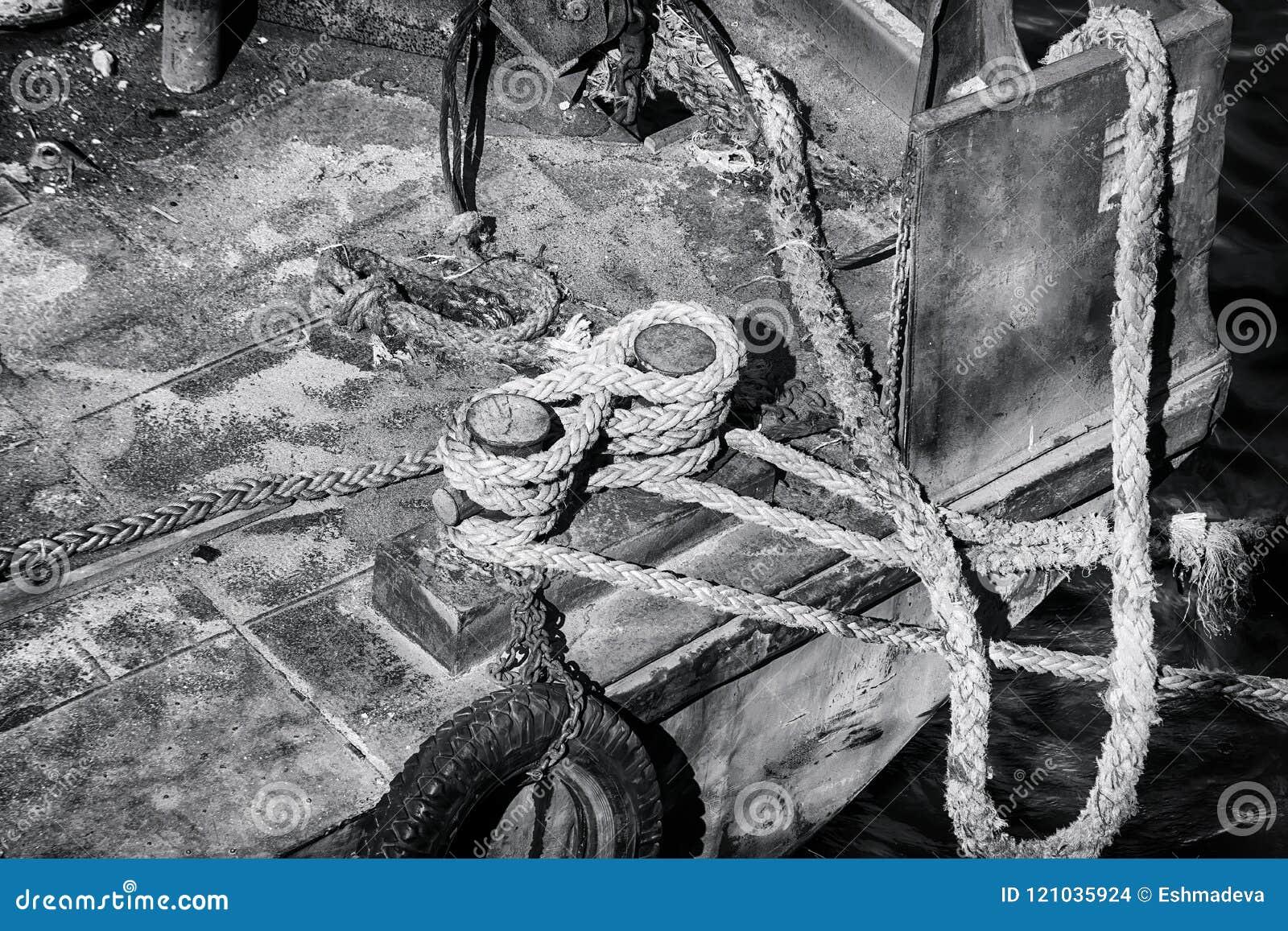 Poste de amarração velho e corda forte no cais abandonado