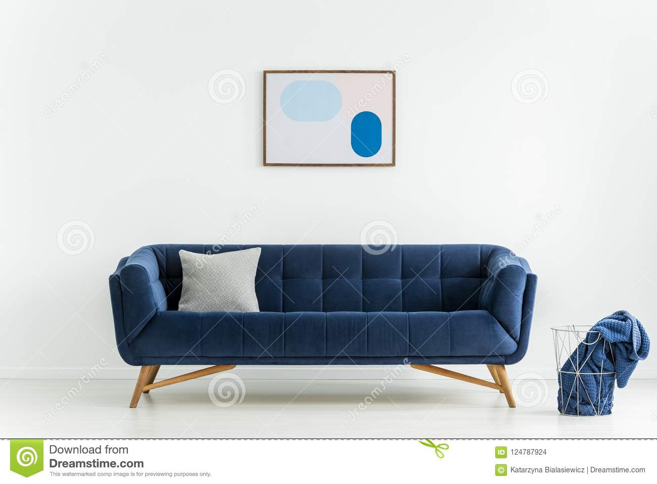 Poster above blue sofa with cushion in white living room interior with blanket in basket. Real photo