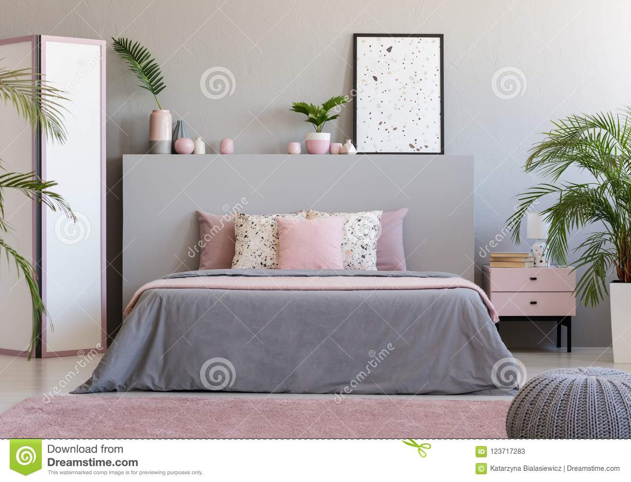 Poster On Grey Headboard Of Bed In Grey And Pink Bedroom