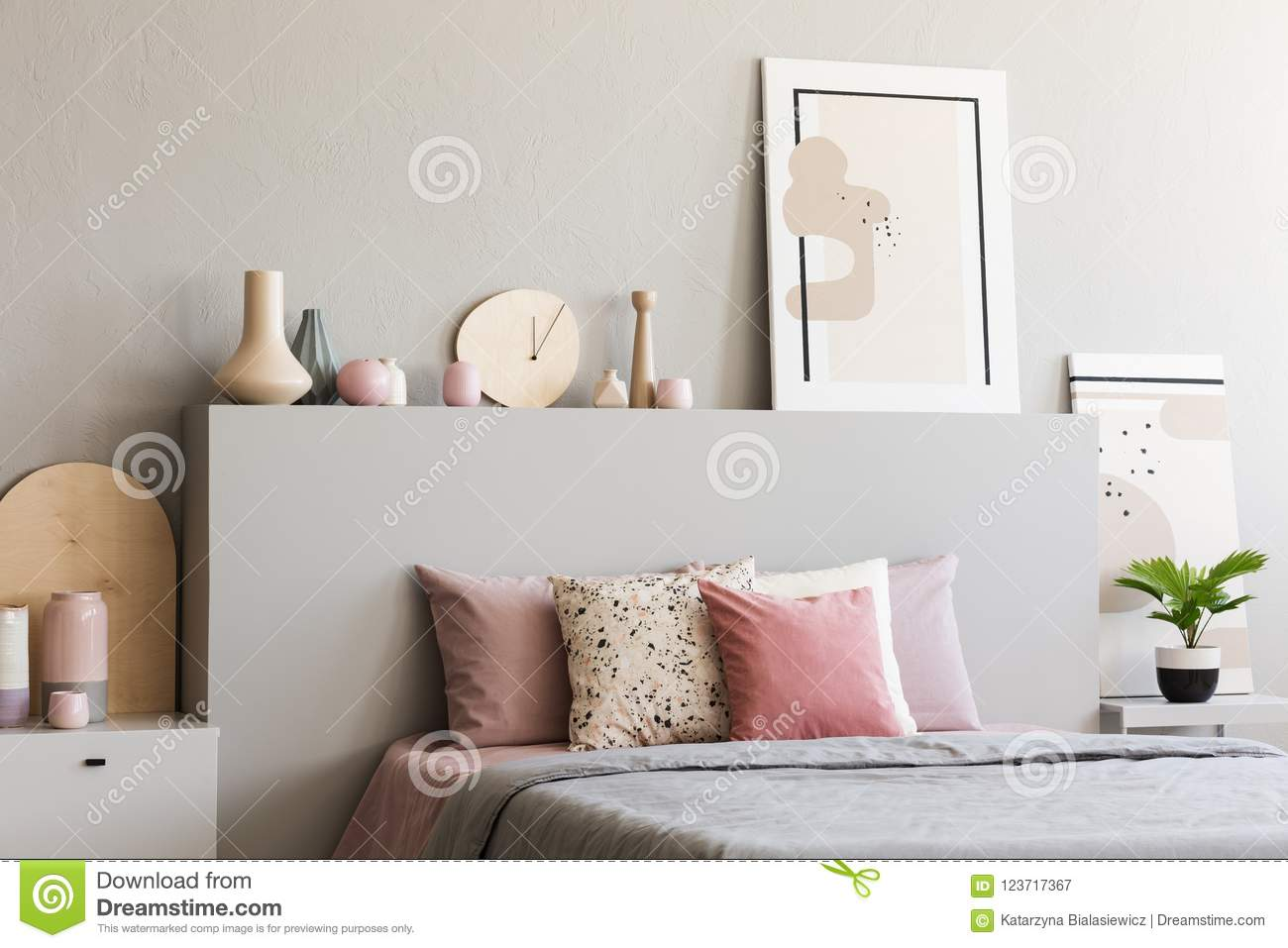 Poster On Headboard Of Bed With Pink Cushions In Grey Bedroom In ...