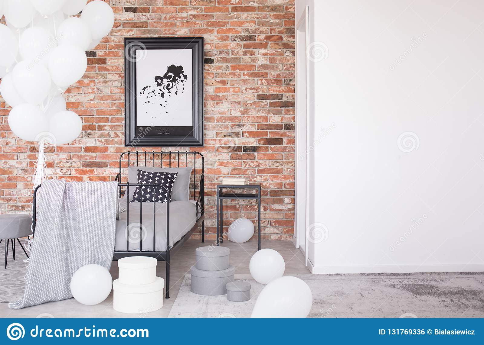 Poster on red brick wall above bed in interior with copy space and balloons. Real photo