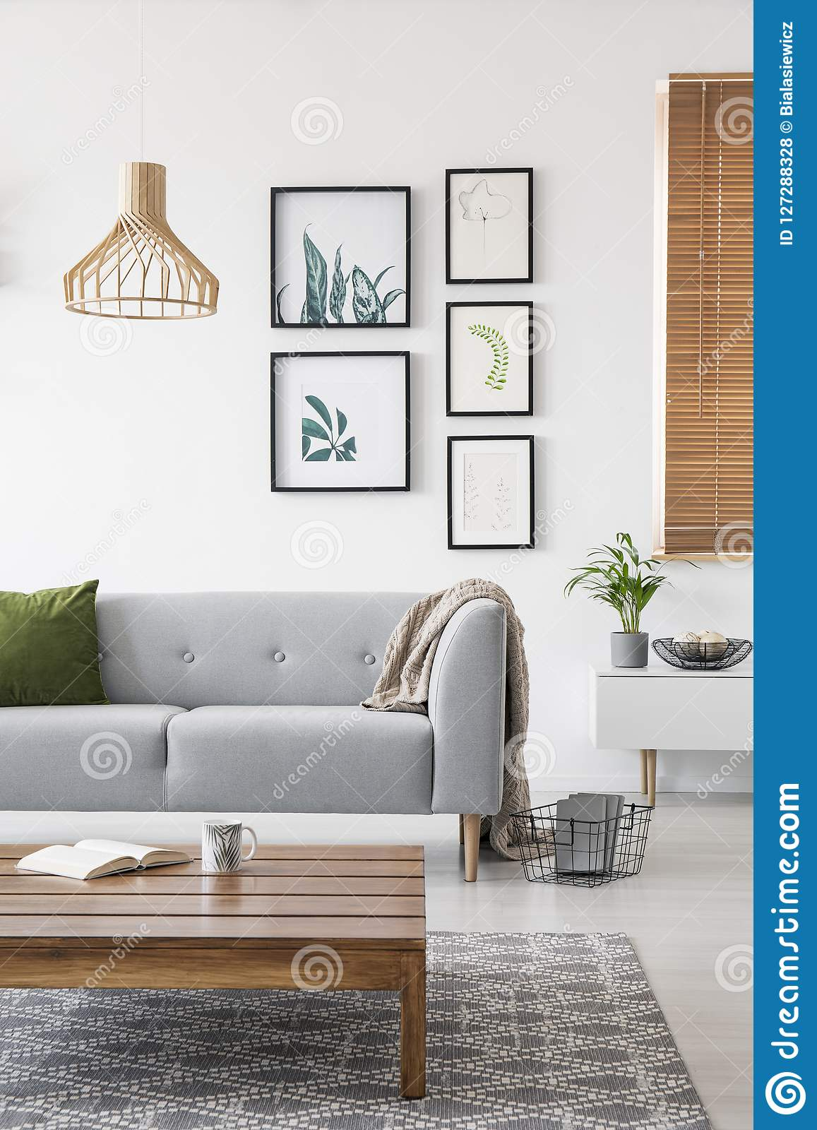 posters on a wall in a living room interior with a sofa