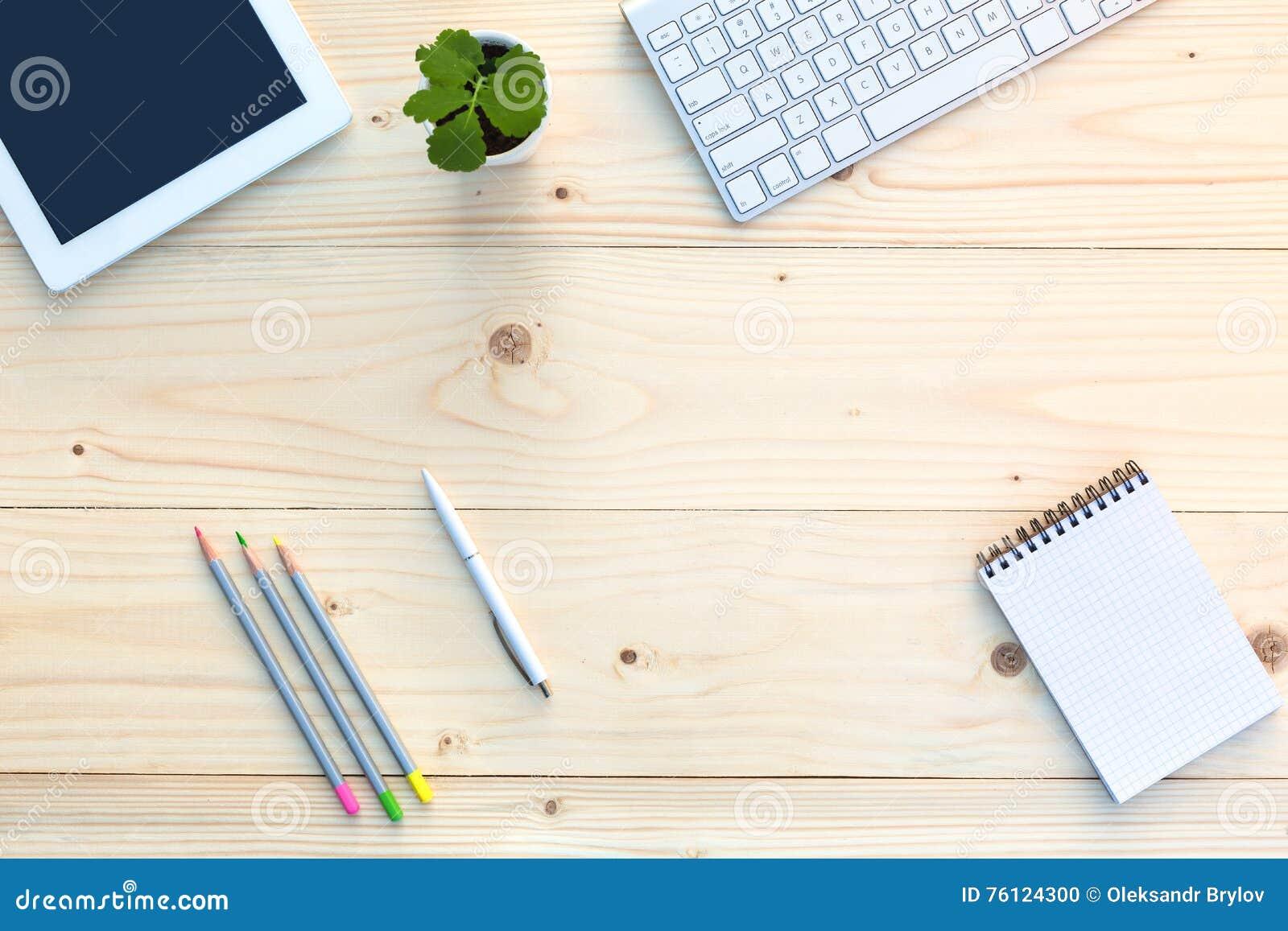 Posto di lavoro sullo scrittorio di legno leggero con elettronica ed il fiore della cancelleria