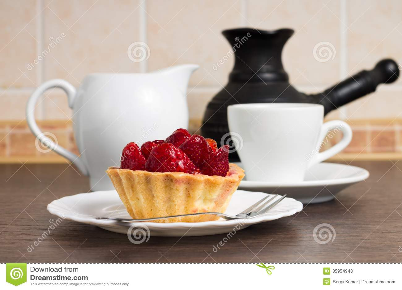 Postre de la fresa con la taza de café