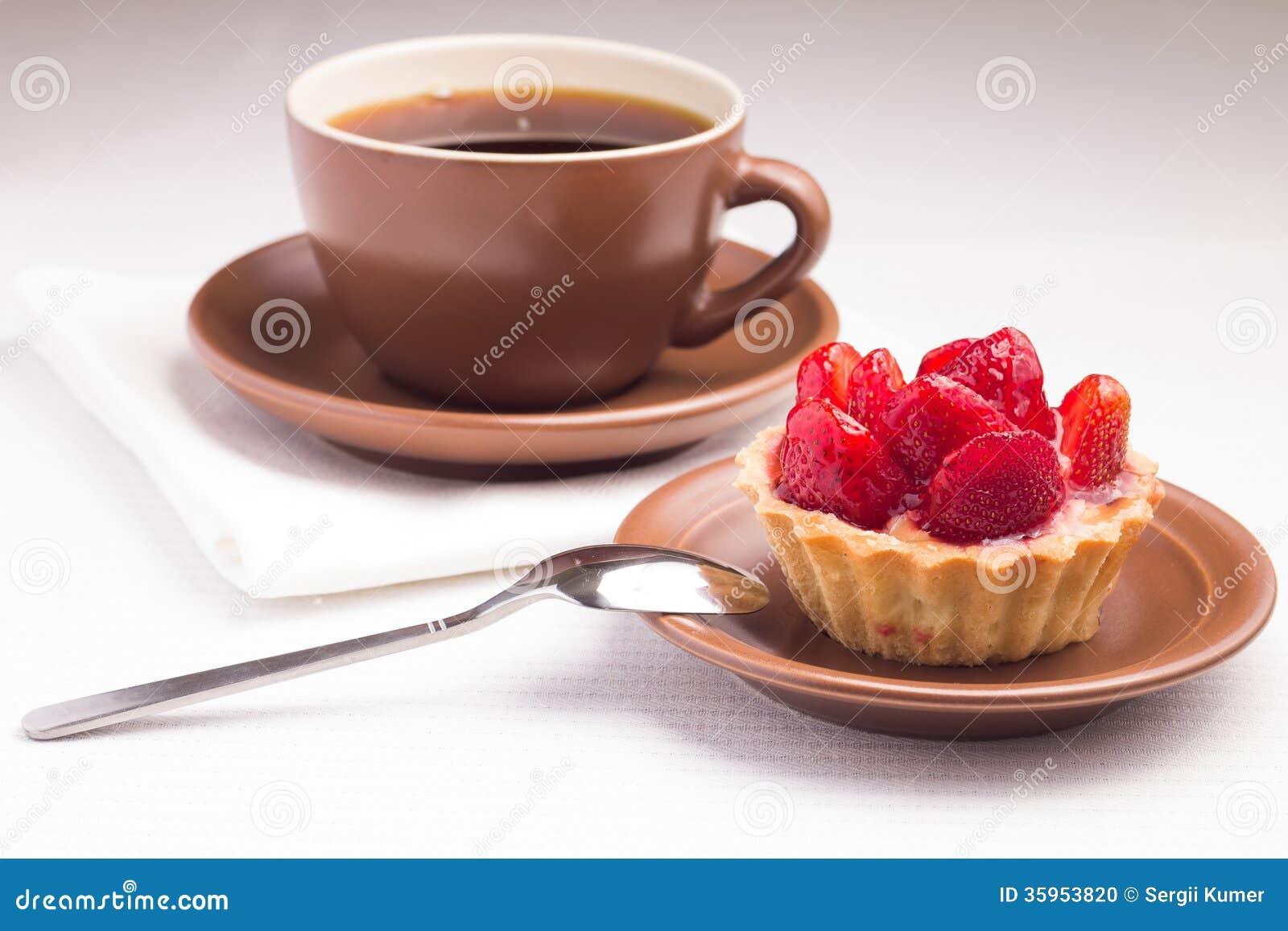 Postre de la fresa con la taza de té caliente