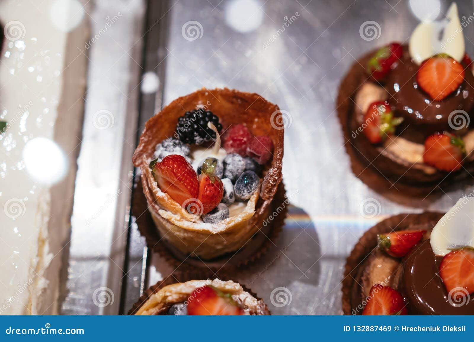 Postre de los tartlets de la fruta y de la baya en fondo clasificado bandeja de la visión superior