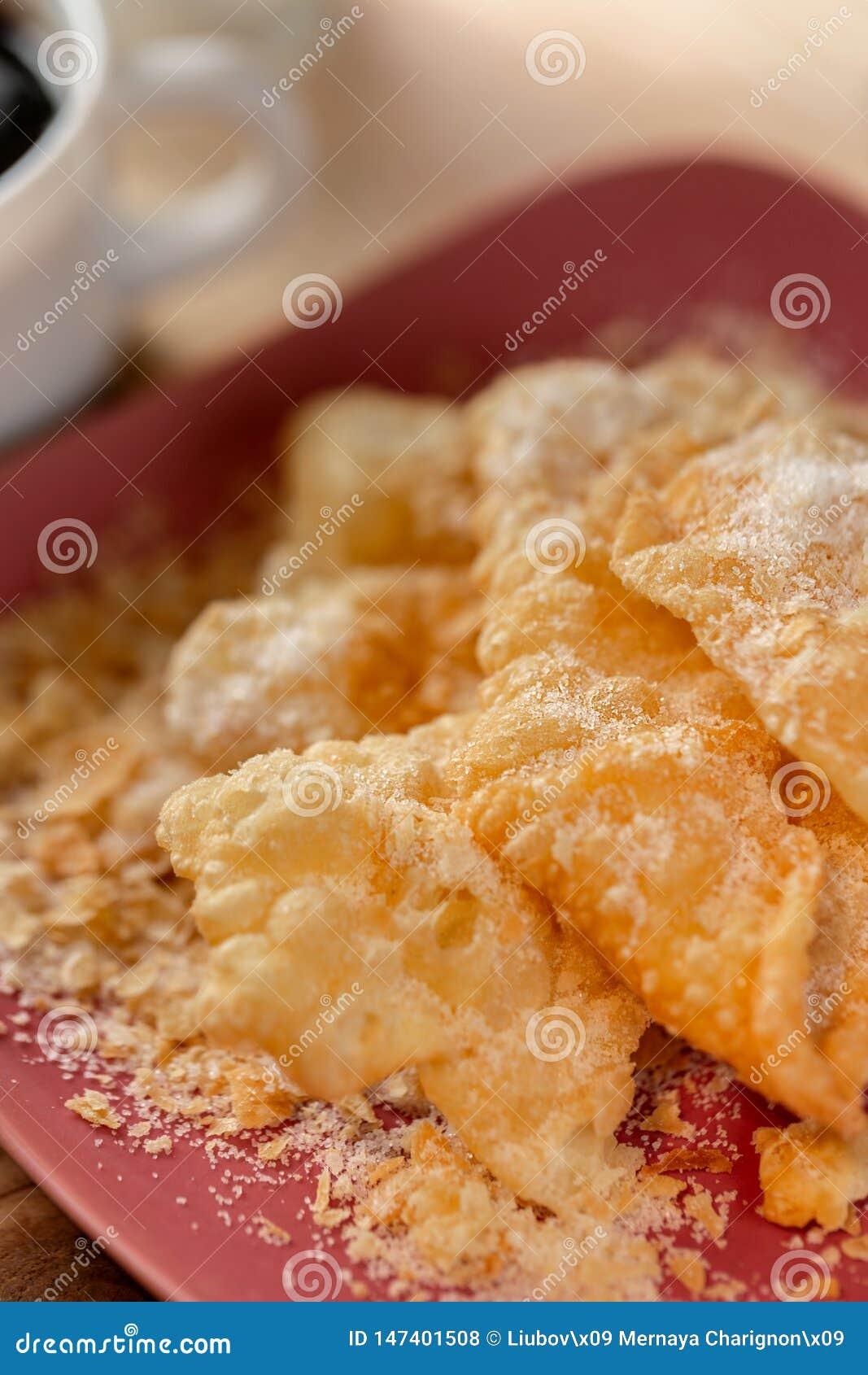 Postre Galletas curruscantes Crackled con el az?car en una placa y una taza de caf? en una tabla de madera