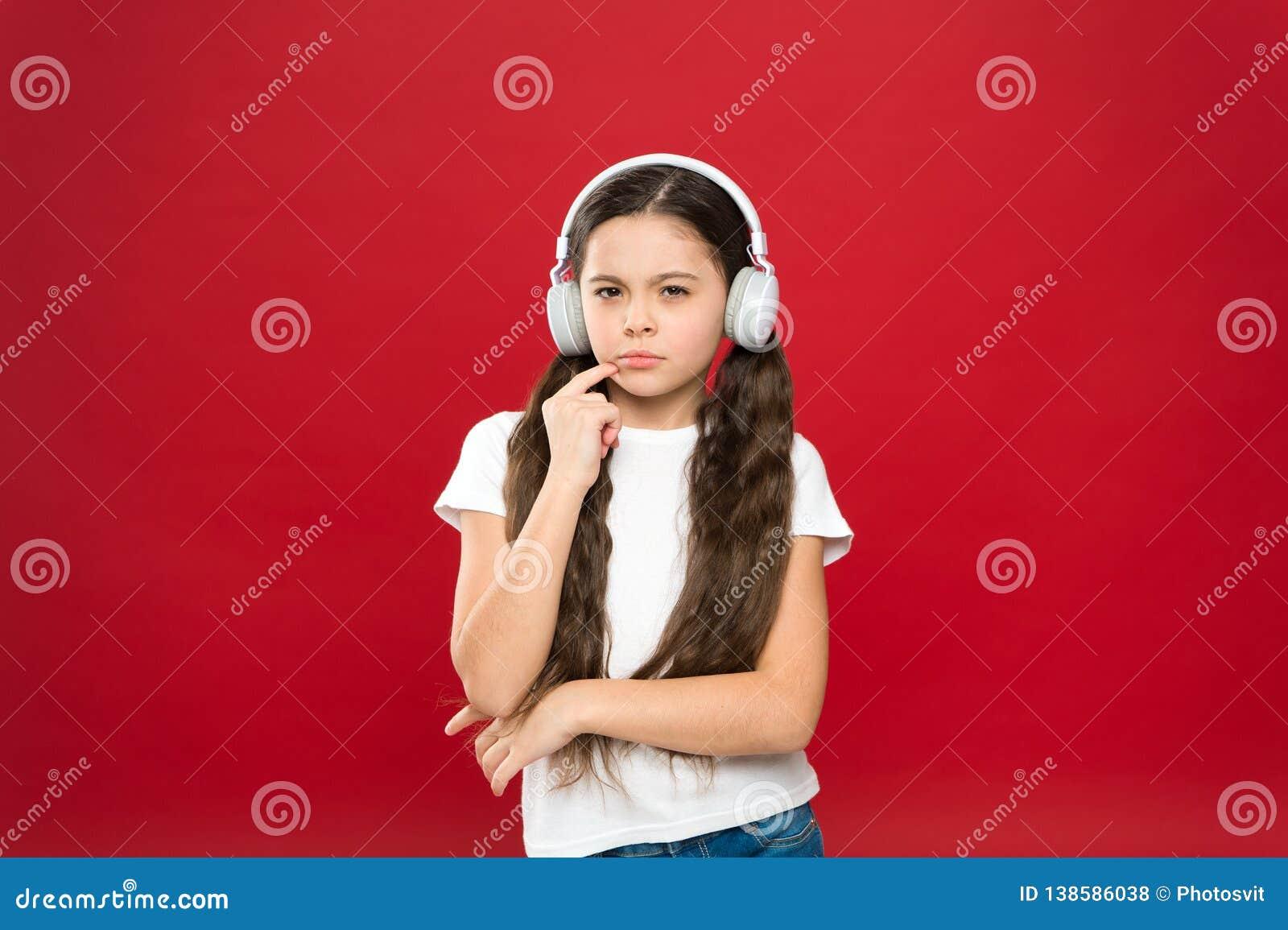 Potężnego skutka muzyczni nastolatkowie ich emocje, postrzeganie świat Dziewczyna słucha muzycznych hełmofony na czerwonym tle
