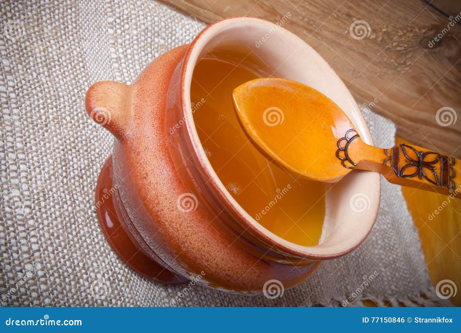 Pot d argile avec le ghee et la cuillère sur la serviette de toile Toujours durée rustique