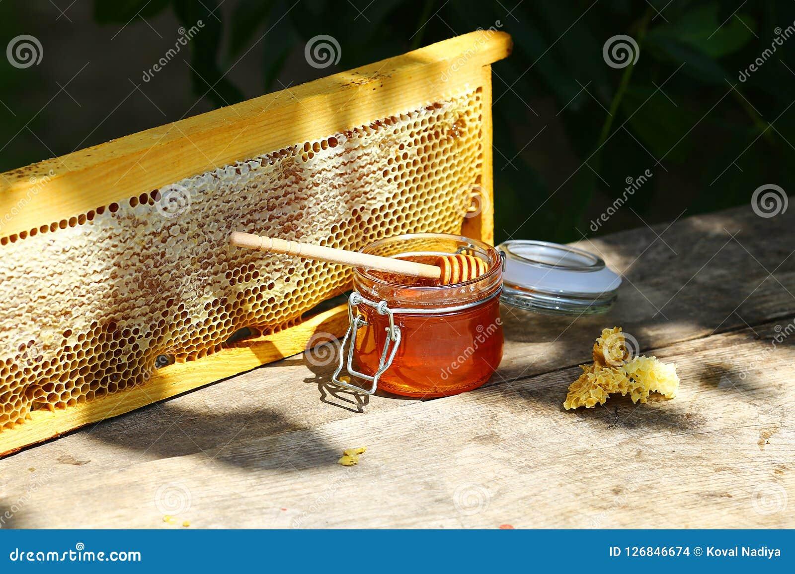 Pot de miel frais dans un pot en verre sur une vieille table sur un rucher outside cadre avec la structure de cire d abeilles com