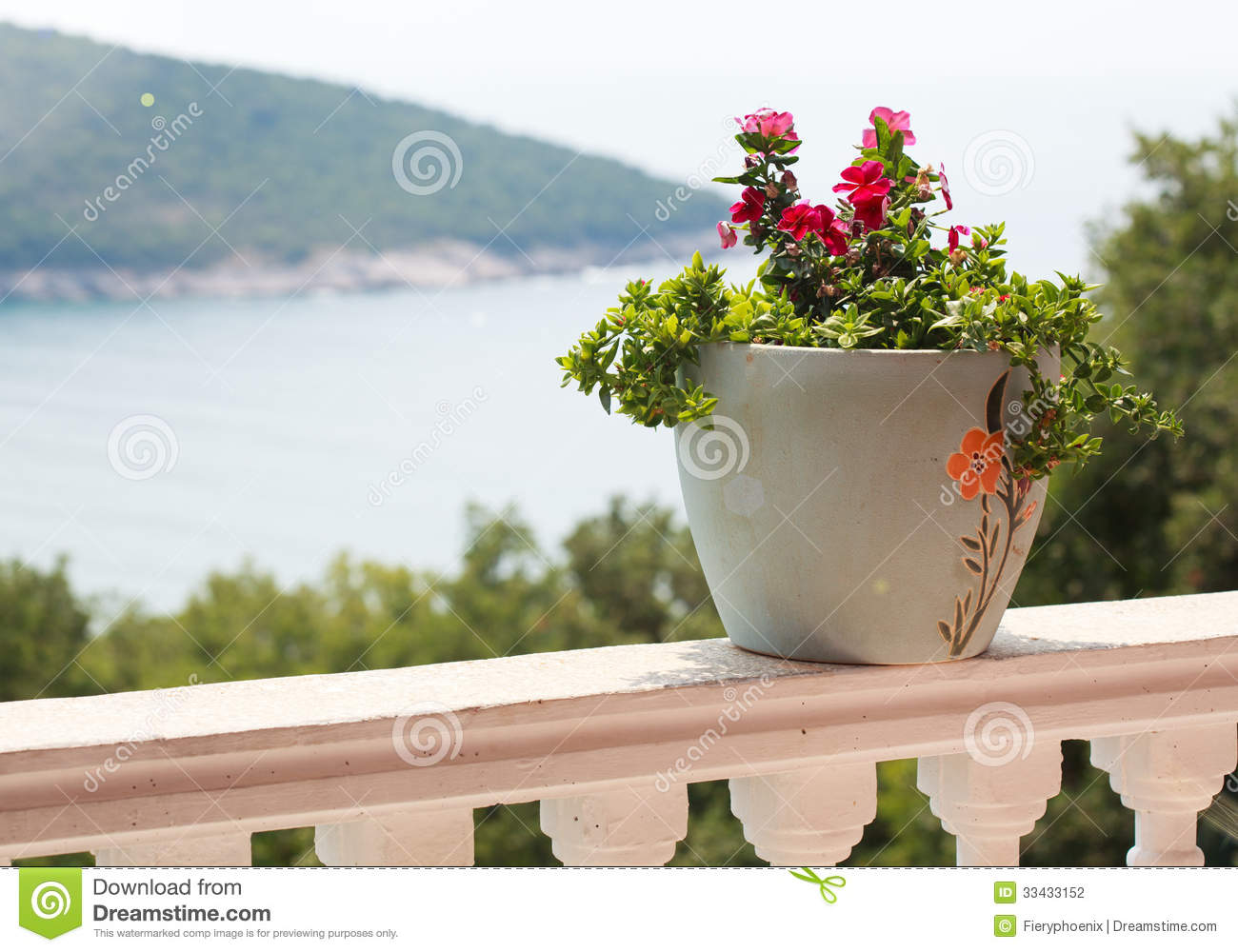 A Pot Of Flowers On The Balcony Balustrade With A