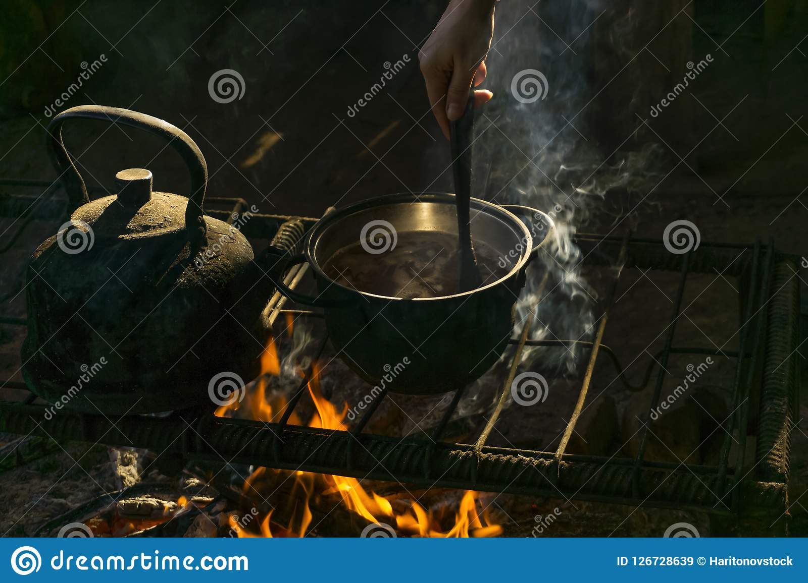 Pot and kettle on a portable hearth made of metal rods in a nomad`s dwelling. Pot and kettle stand over a fire on a portable hearth made of metal rods in a nomad Royalty Free Stock Images