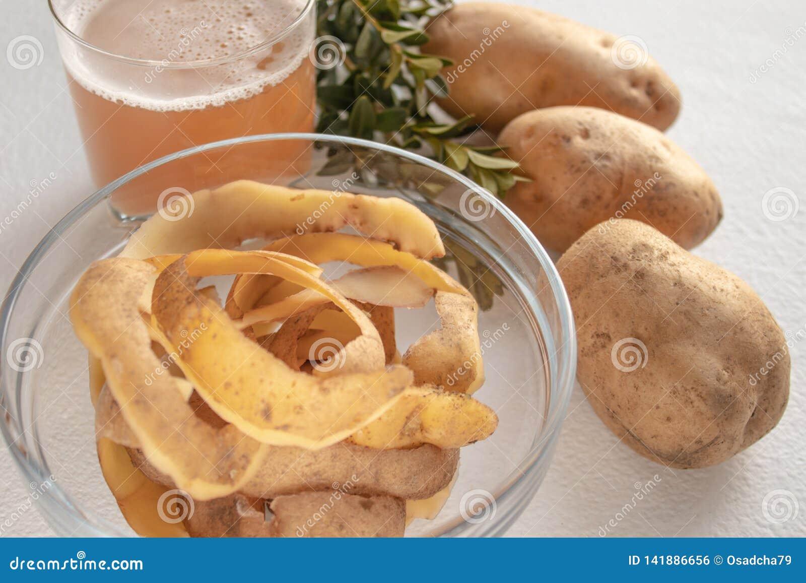 Potatisfruktsaft i ett exponeringsglas nära den hela potatisen och skarlupaen