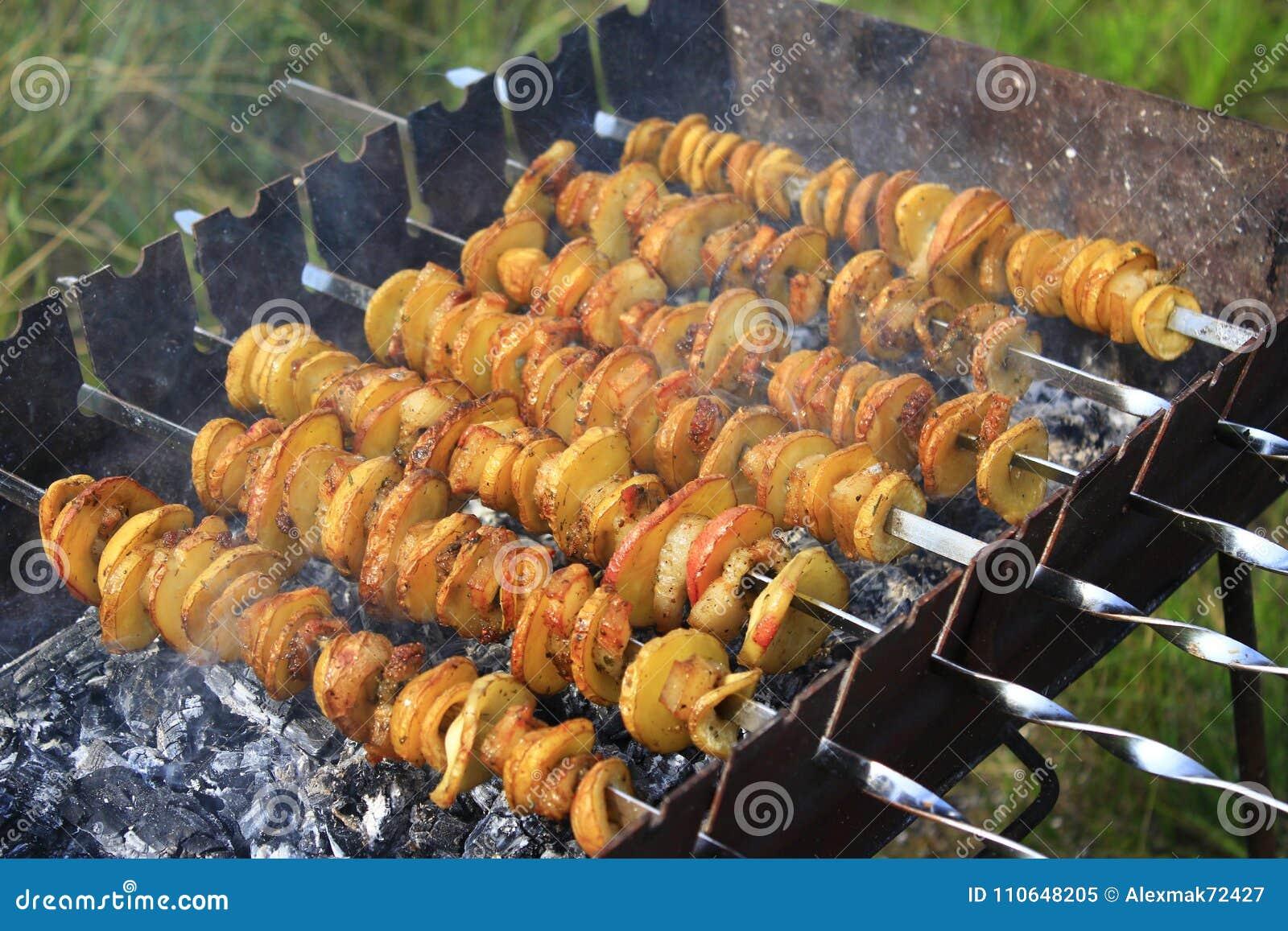 Potatissteknålar med bacon Marinerad shashlik som förbereder sig på grillfestgaller över kol