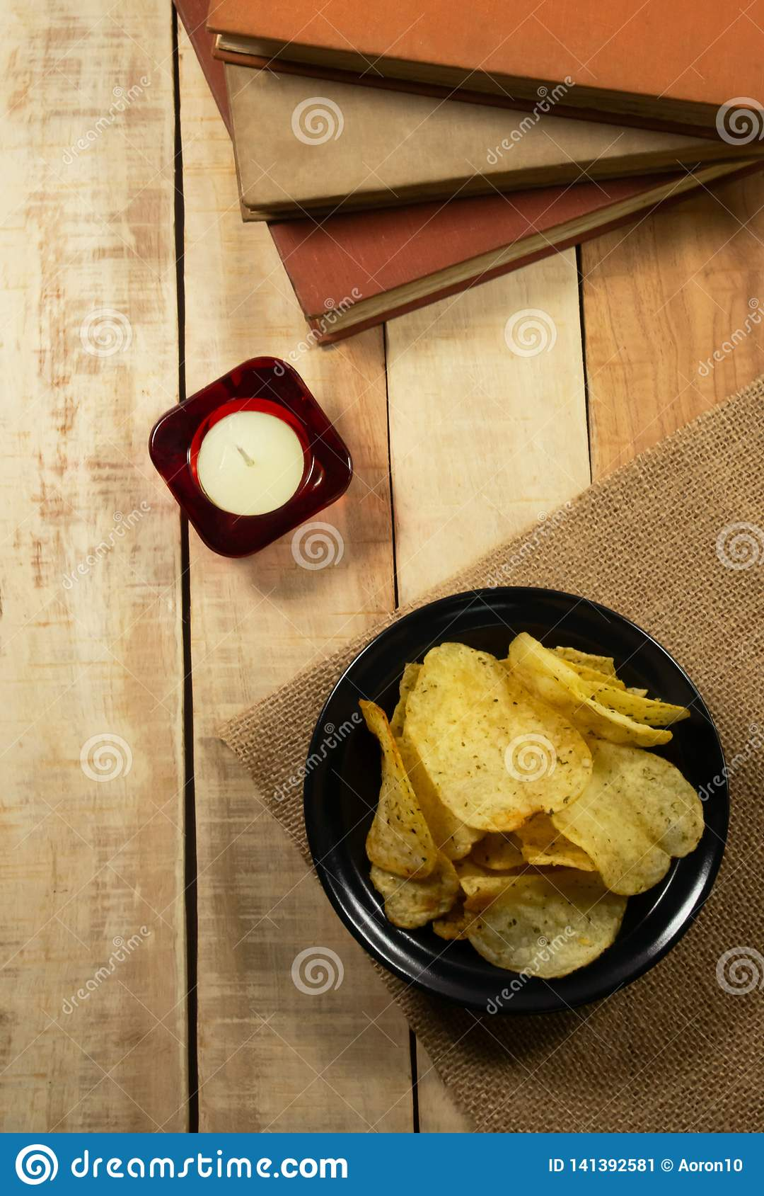 Potato chips in a black bowl, aromatherapy candles and books on a wooden floor.