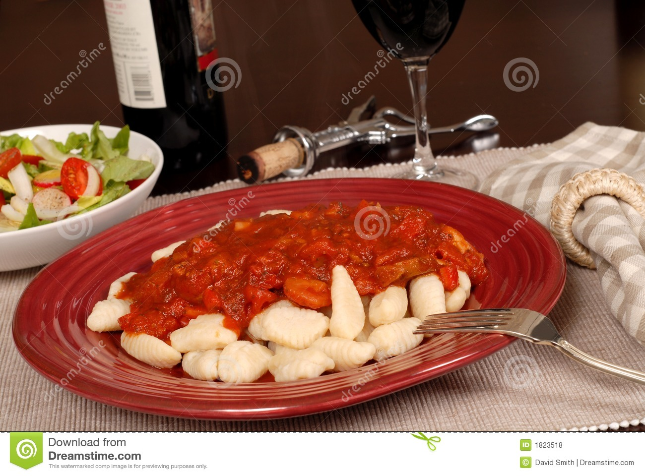 ... Stock Photos: Potato gnocchi with marinara sauce with a salad and wine