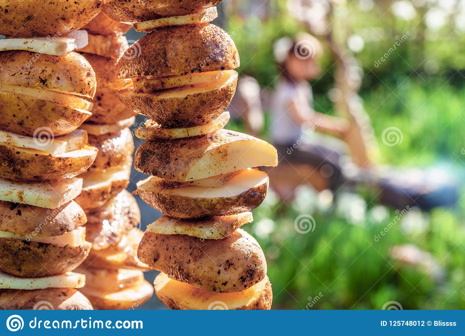 Potato with lard on skewers prepared for roasting on fire at picnic