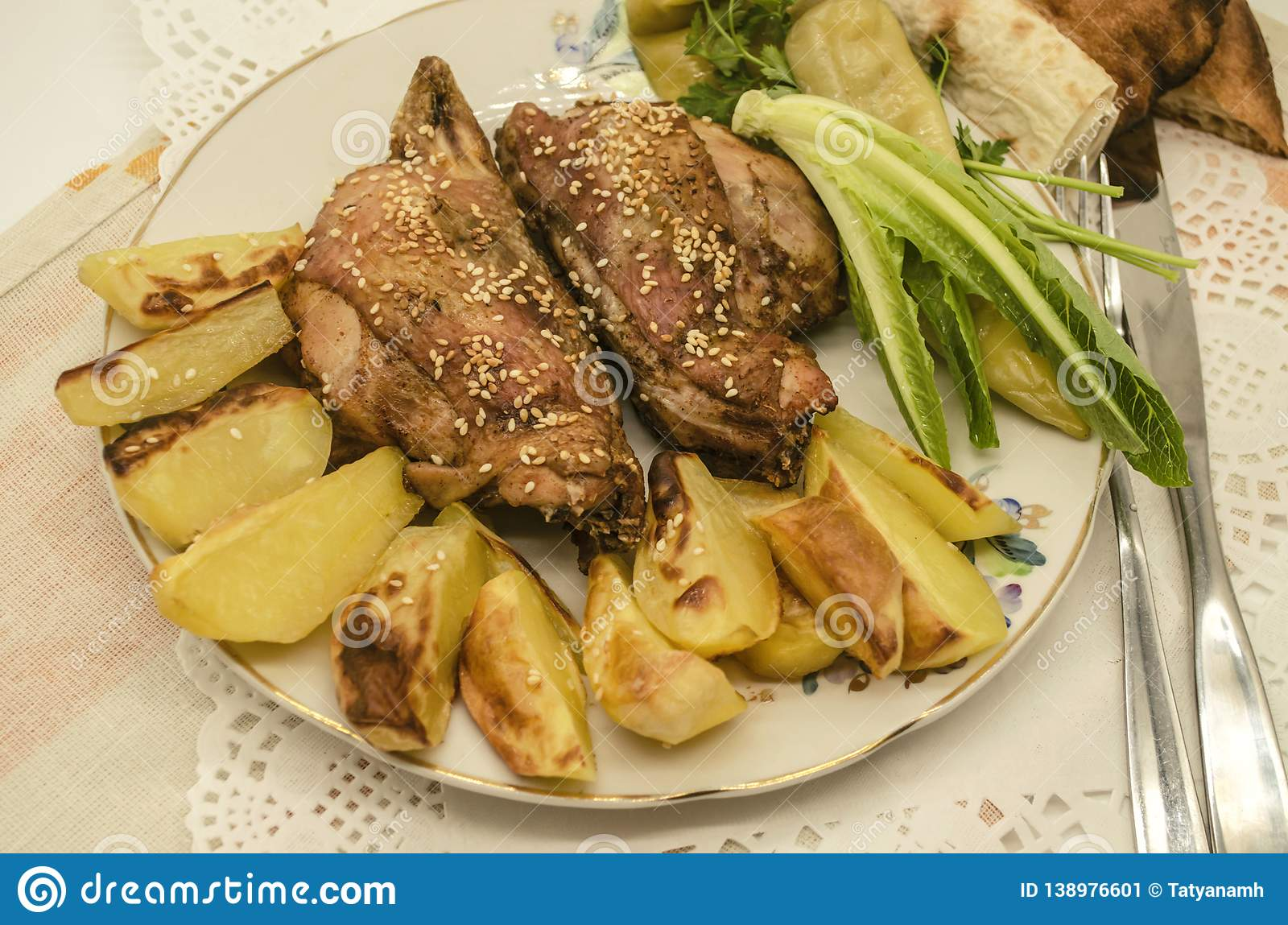 Potatoes with chicken covered with white sesame, black pepper and salad on a faience plate,are lying on a white paper napkin. Baked potatoes and chicken stock image