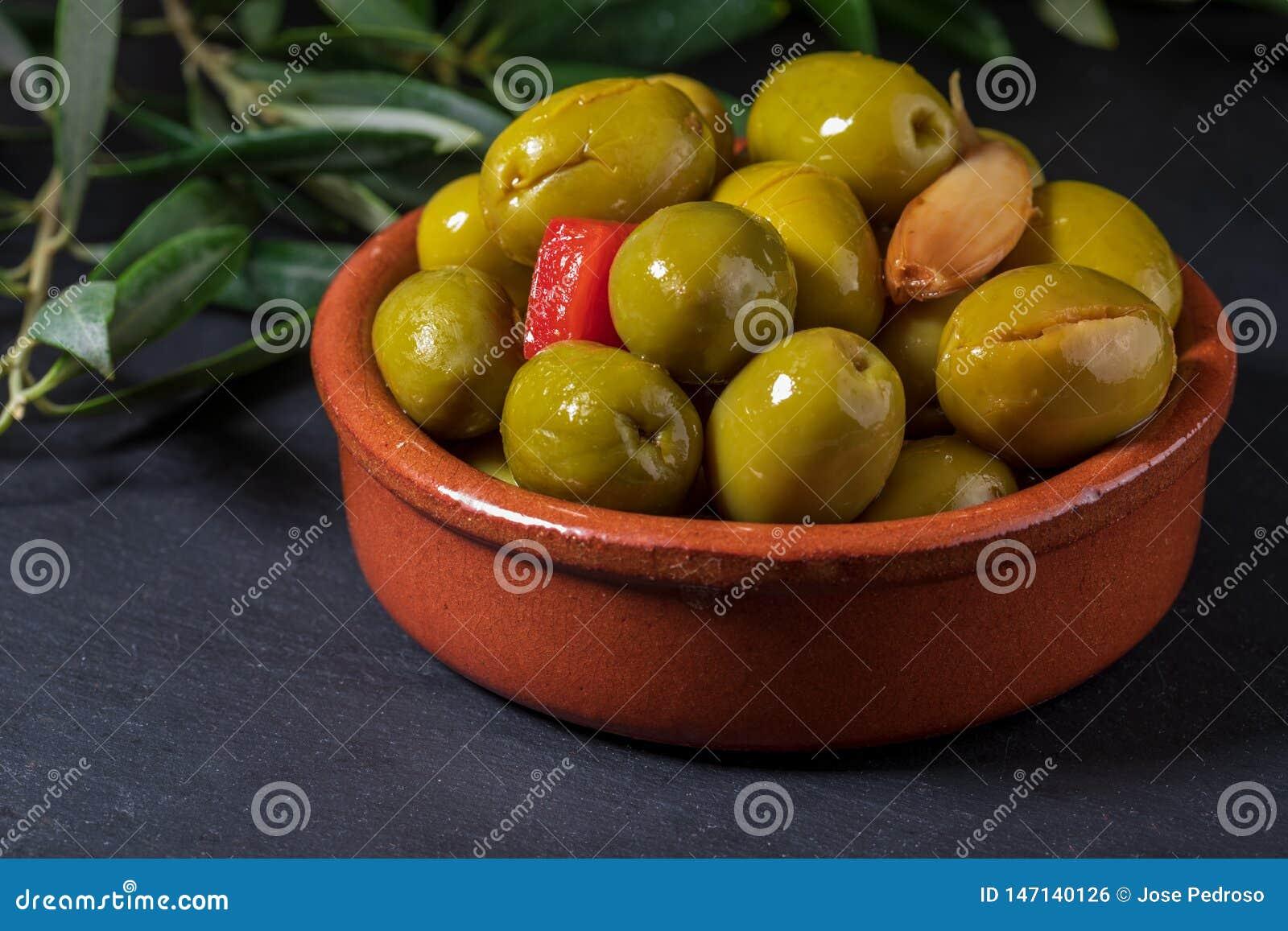 Pote de arcilla con las aceitunas del artesano preservadas en aceite de oliva virginal adicional, vinagre, especias con las pimie