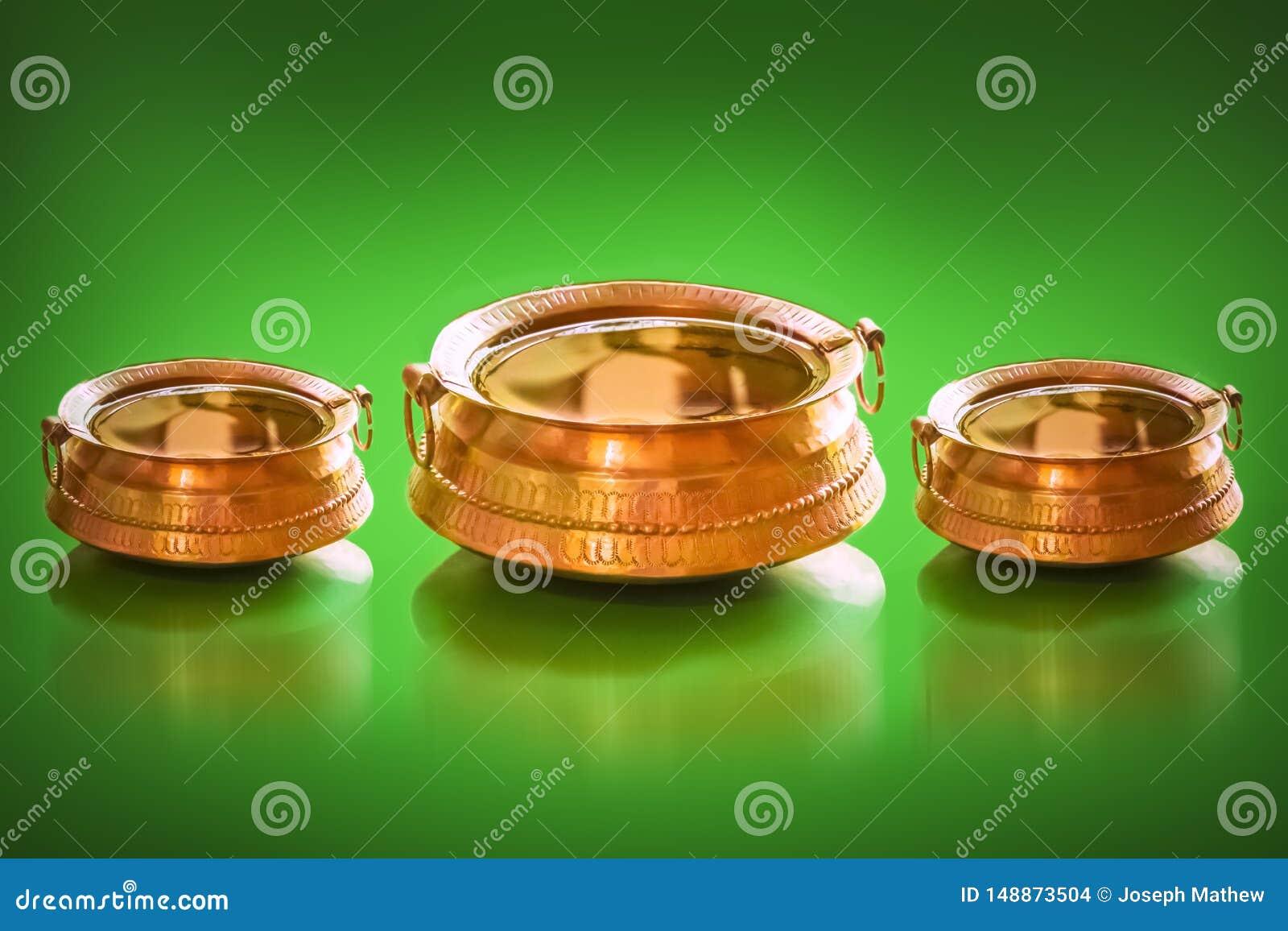 Pote de cobre amarillo tradicional con lleno de interior del agua y de las monedas para el encanto afortunado