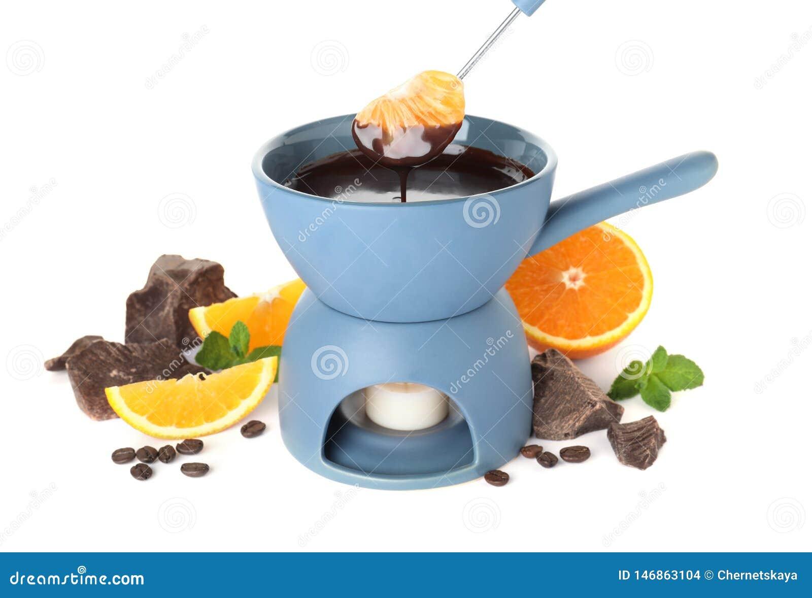 Pote de la  fondue  con el chocolate y las frutas en blanco