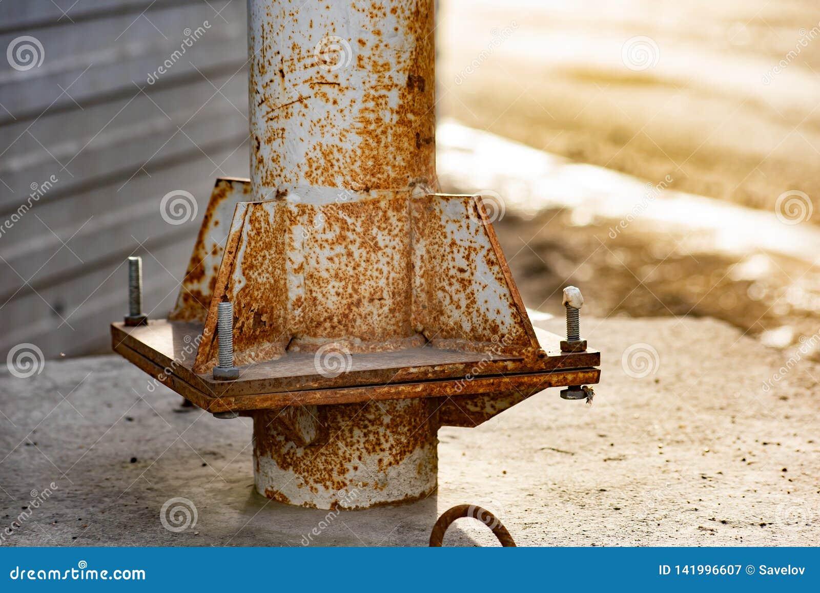 Poteau rouillé en métal avec des boulons et des écrous