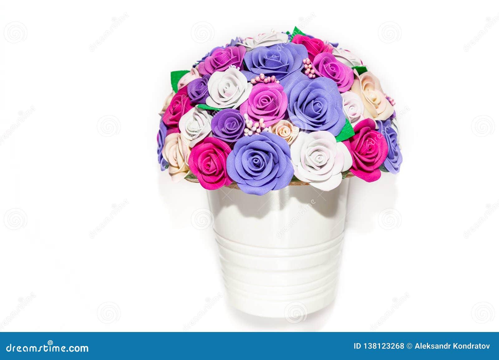 Potenciômetro branco bonito das flores em um fundo vazio com as rosas decorativas coloridos das cores do rosa, as roxas e as lilá