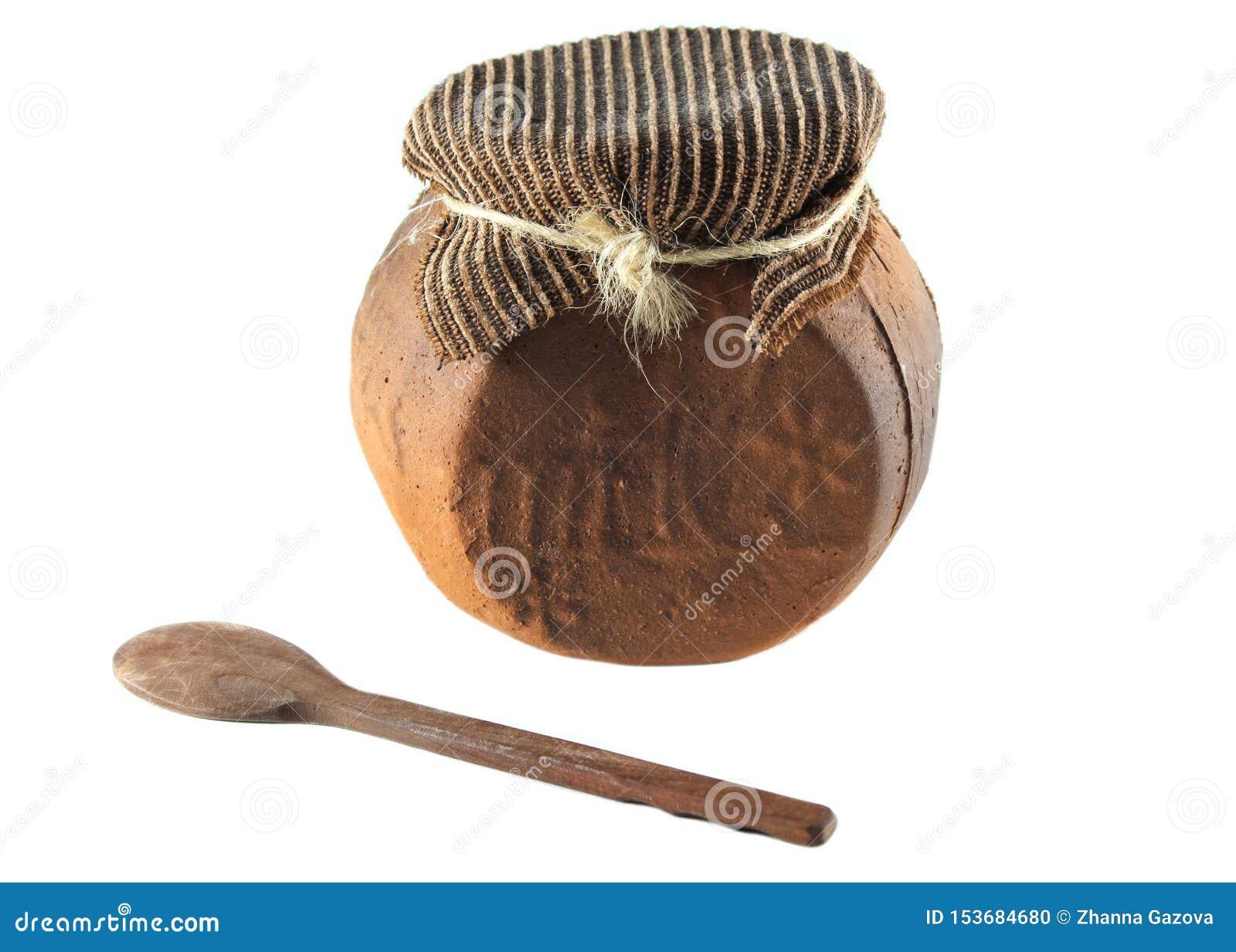 Potenci?metro cer?mico vitrificado para cozinhar com colher de madeira em um fundo branco