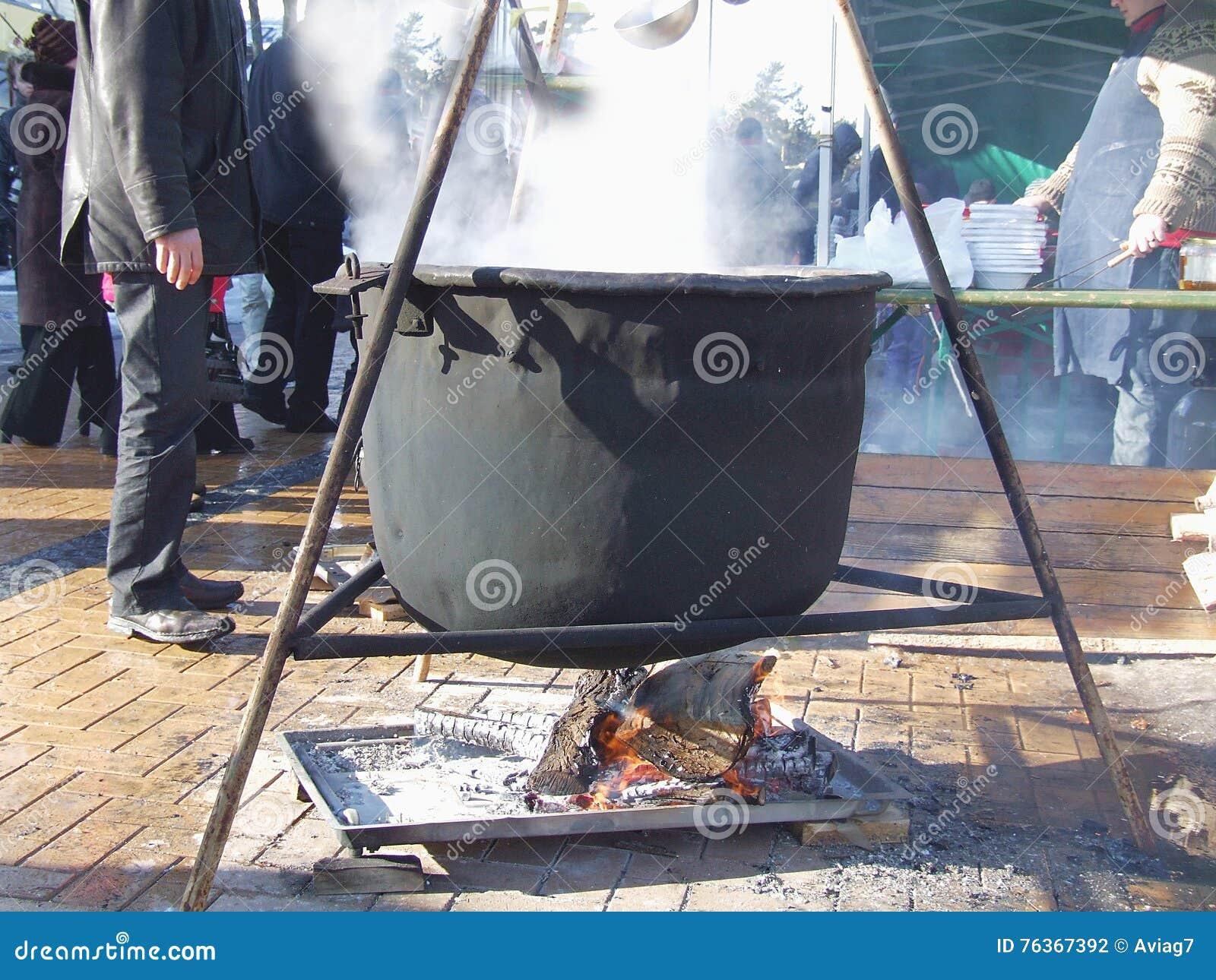 Potenciômetro quente de ebulição do ferro que pendura sobre o fogo aberto