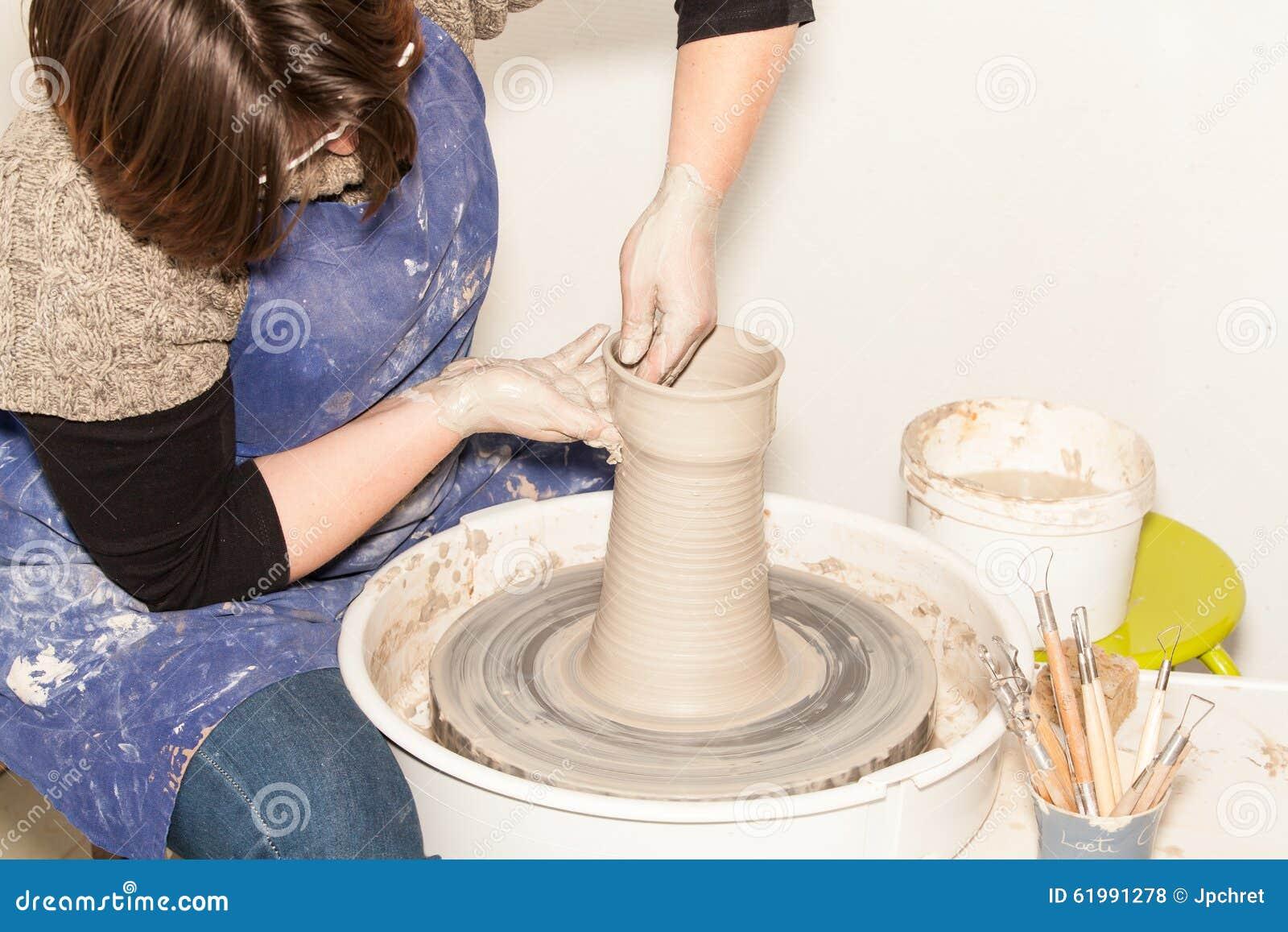 Potier féminin créant un pot de terre sur une roue de potier