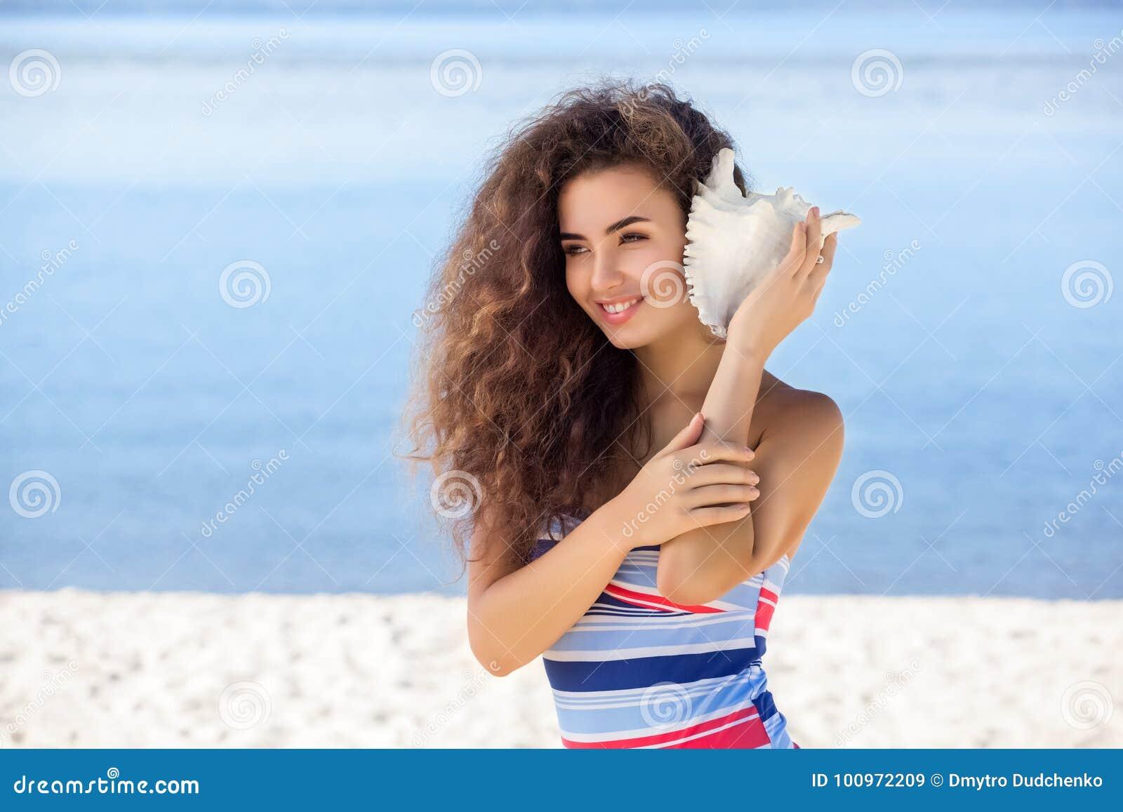 Potomstwa, atrakcyjna dziewczyna z białą skorupą na plaży